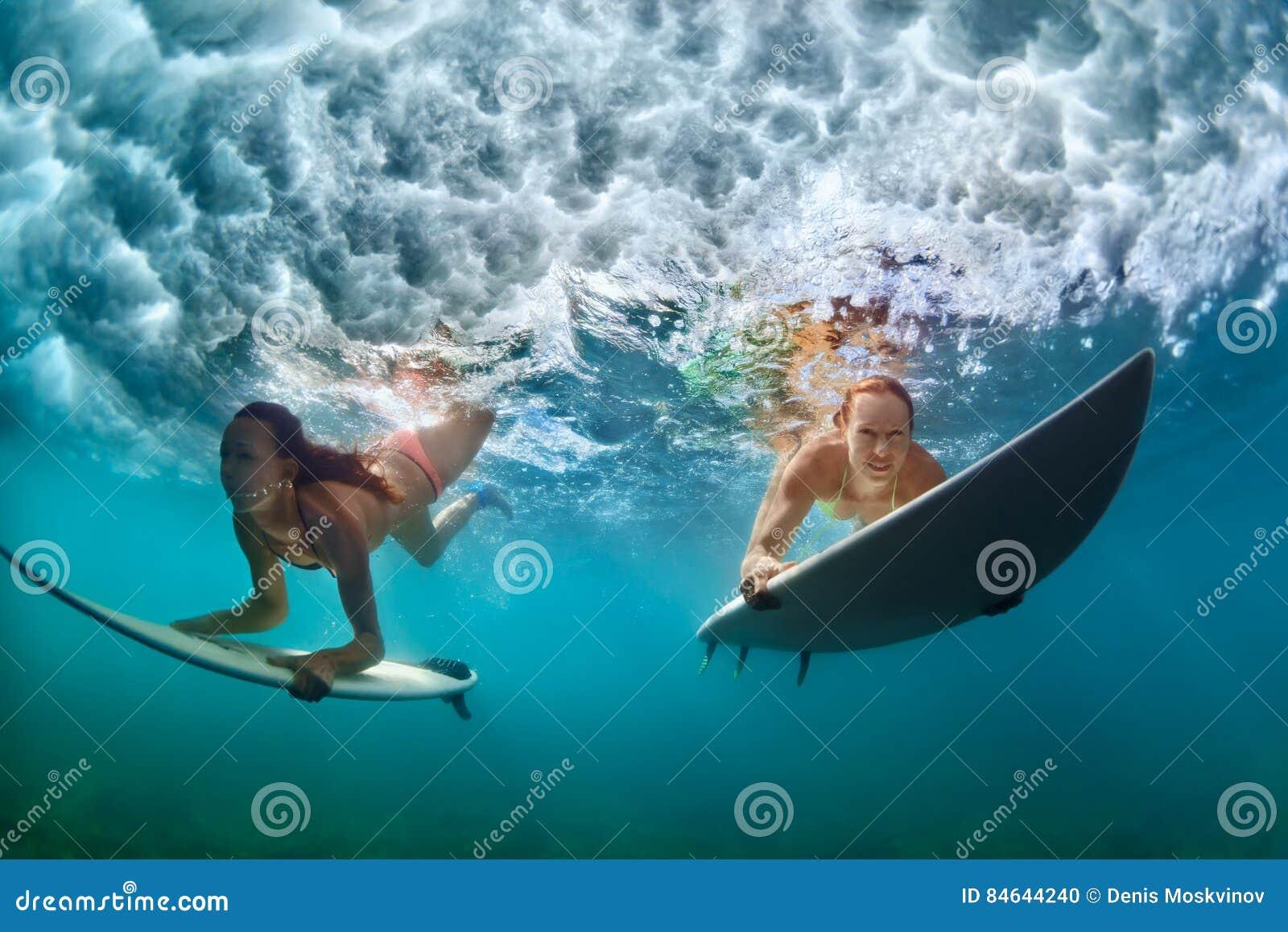 Meninas ativas no biquini na ação do mergulho na placa de ressaca