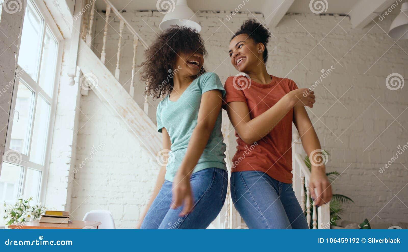 Meninas bonitas novas da raça misturada que dançam em uma cama junto que tem o lazer do divertimento no quarto em casa