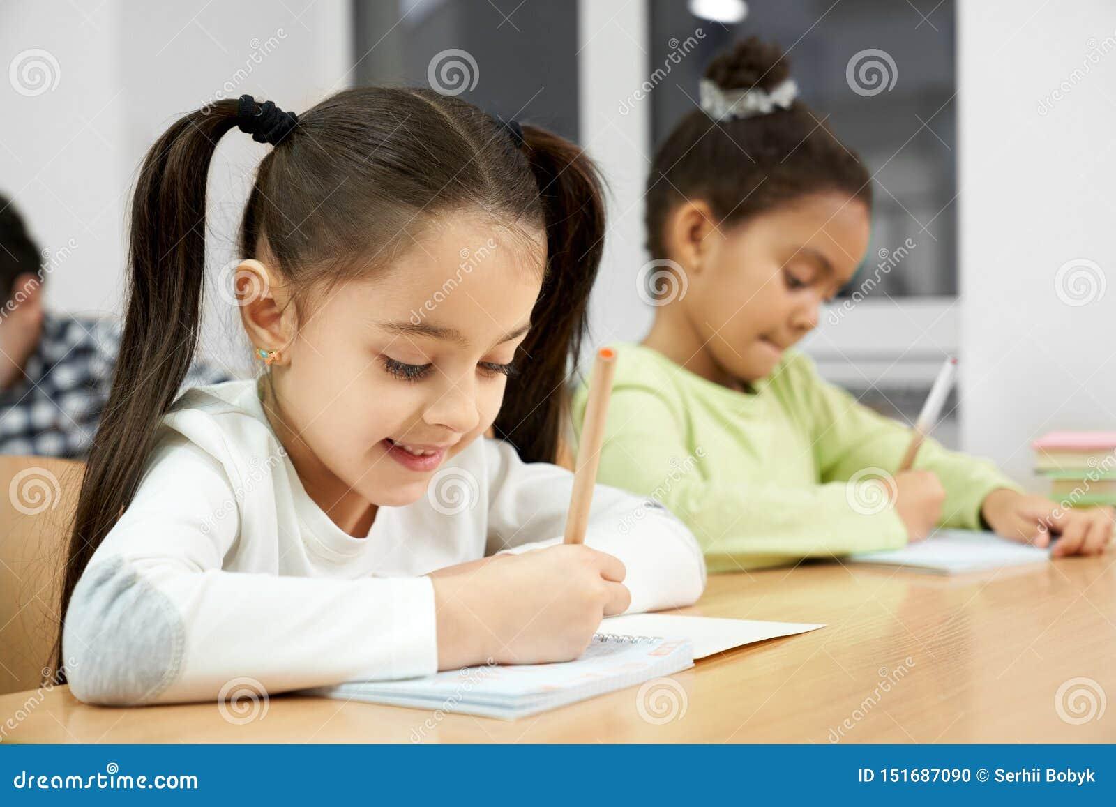 Meninas bonitas que sentam-se na mesa na classe, escrevendo no caderno