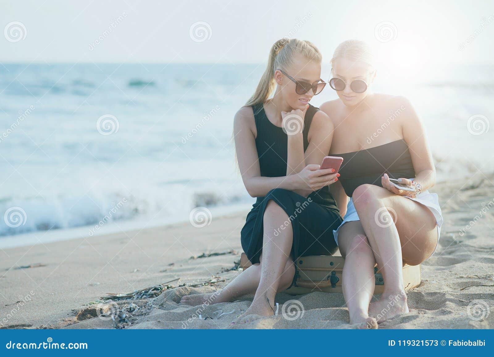 Meninas bonitas que usam o telefone em um Sandy Beach