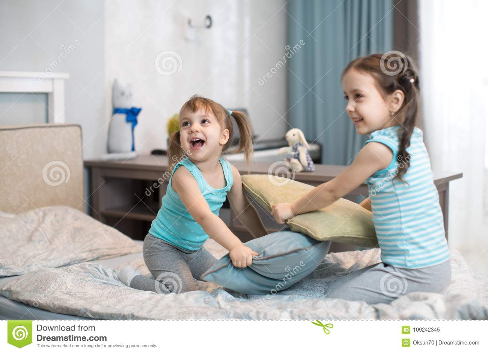 Meninas das crianças que lutam usando descansos no quarto