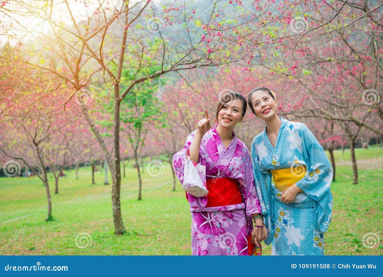 Meninas elegantes felizes que vestem o quimono japonês