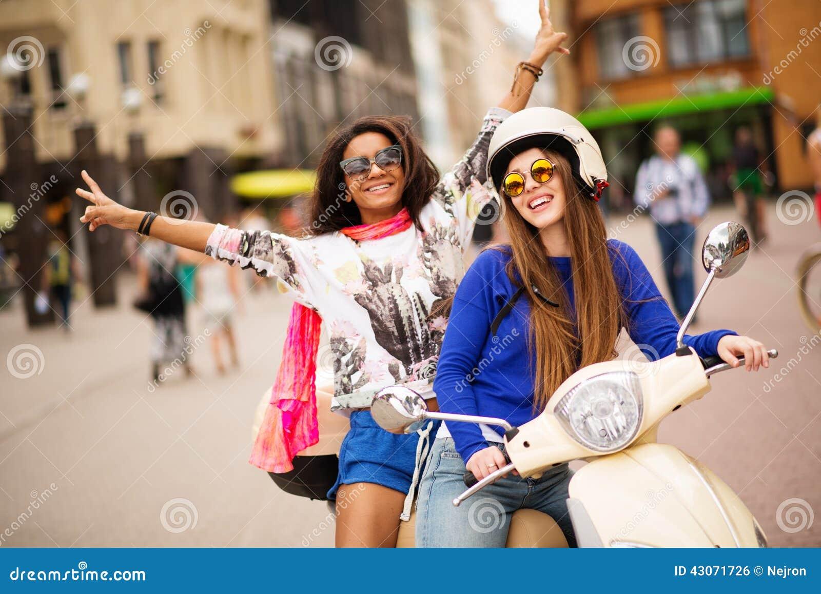 Meninas em um  trotinette  em uma cidade