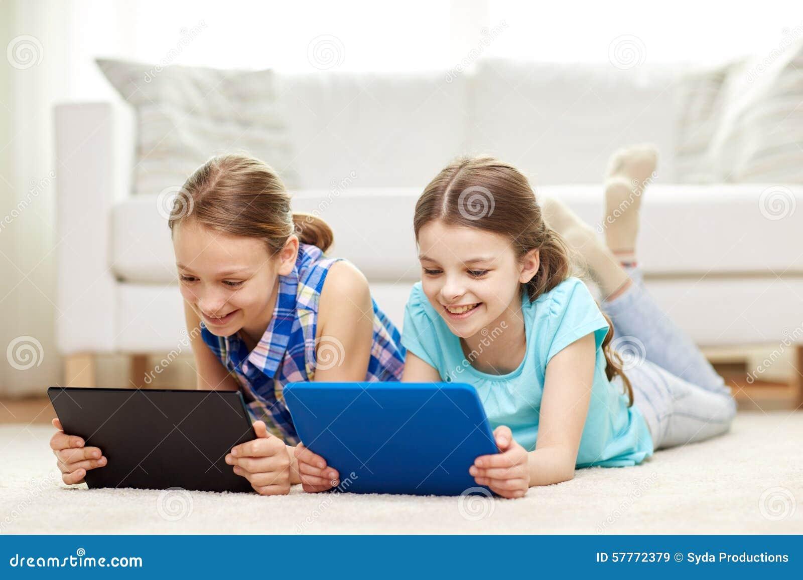 Meninas felizes com o PC da tabuleta que encontra-se no assoalho em casa
