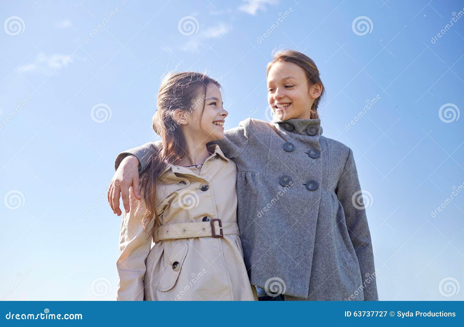 Meninas felizes que abraçam e que falam fora