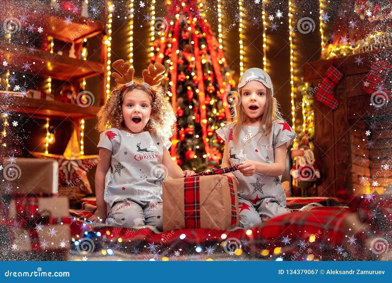 Meninas felizes que vestem a caixa de presente aberta dos pijamas do Natal por uma chaminé em uma sala de visitas escura acolhedo