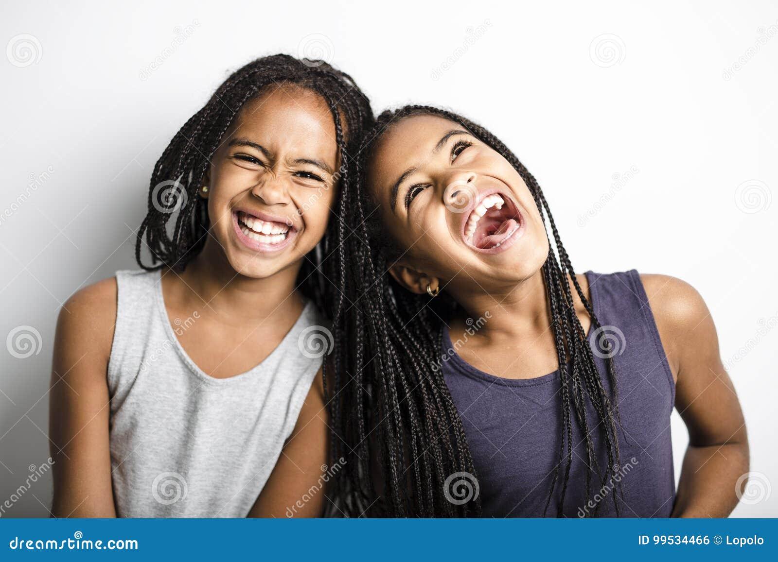 Meninas gêmeas africanas adoráveis no fundo do cinza do estúdio