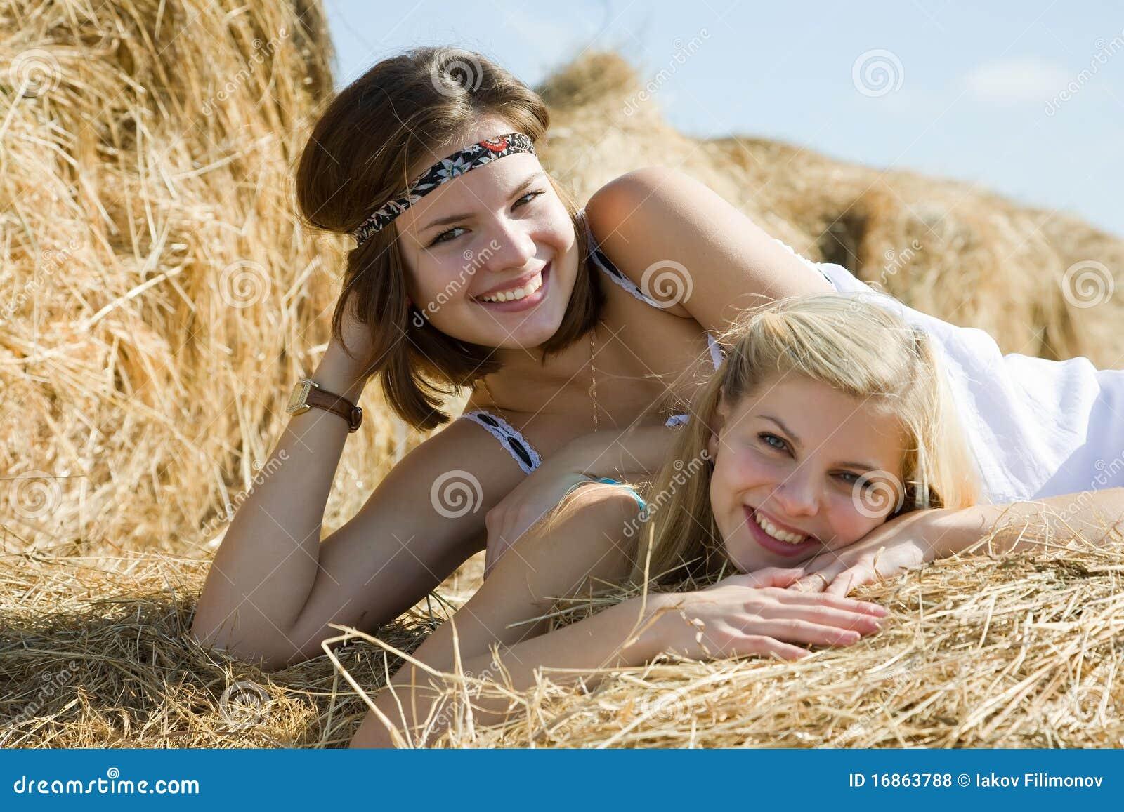 Meninas nos vestidos que descansam no feno
