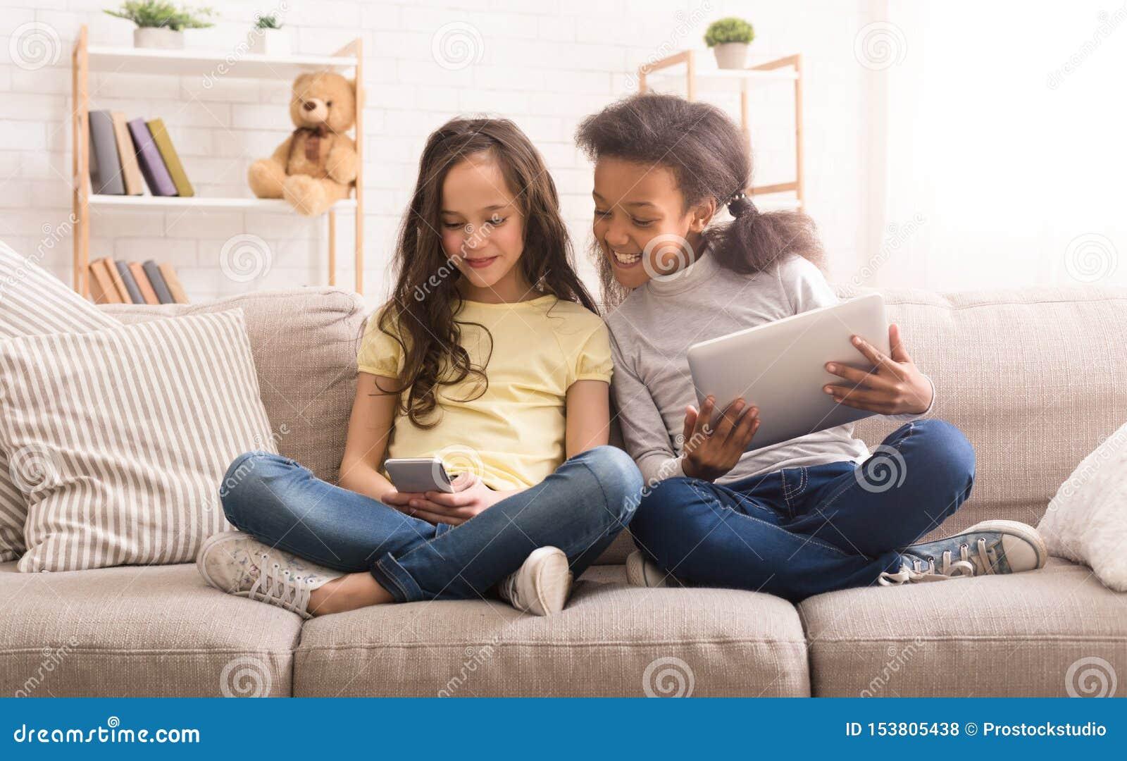 Meninas Preteen com os dispositivos que sentam-se no sofá em casa