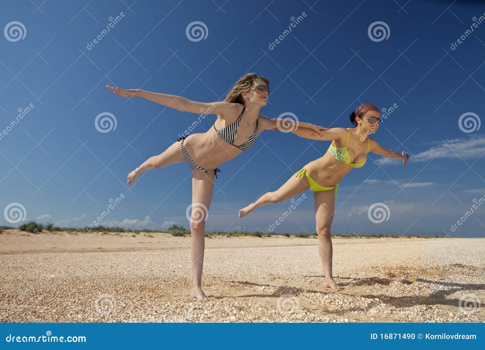 Meninas que exercitam em uma praia