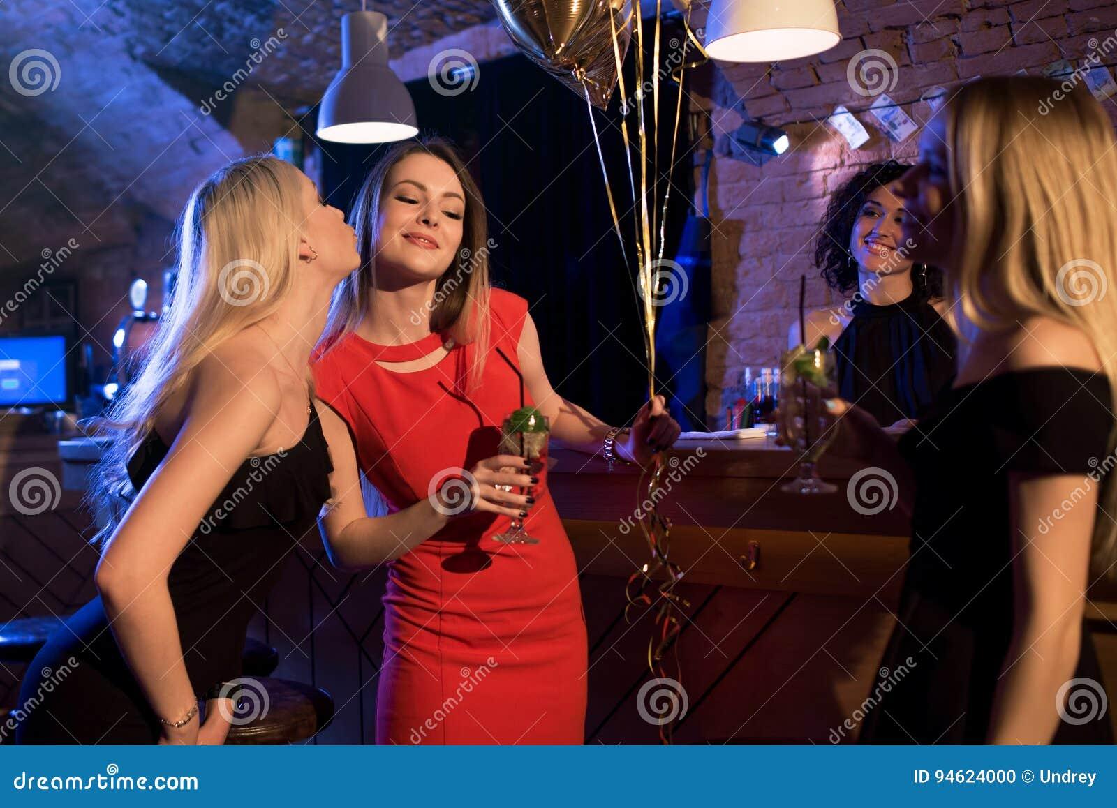 Meninas que felicitam seu amigo com seu aniversário ao comemorar o evento no clube noturno