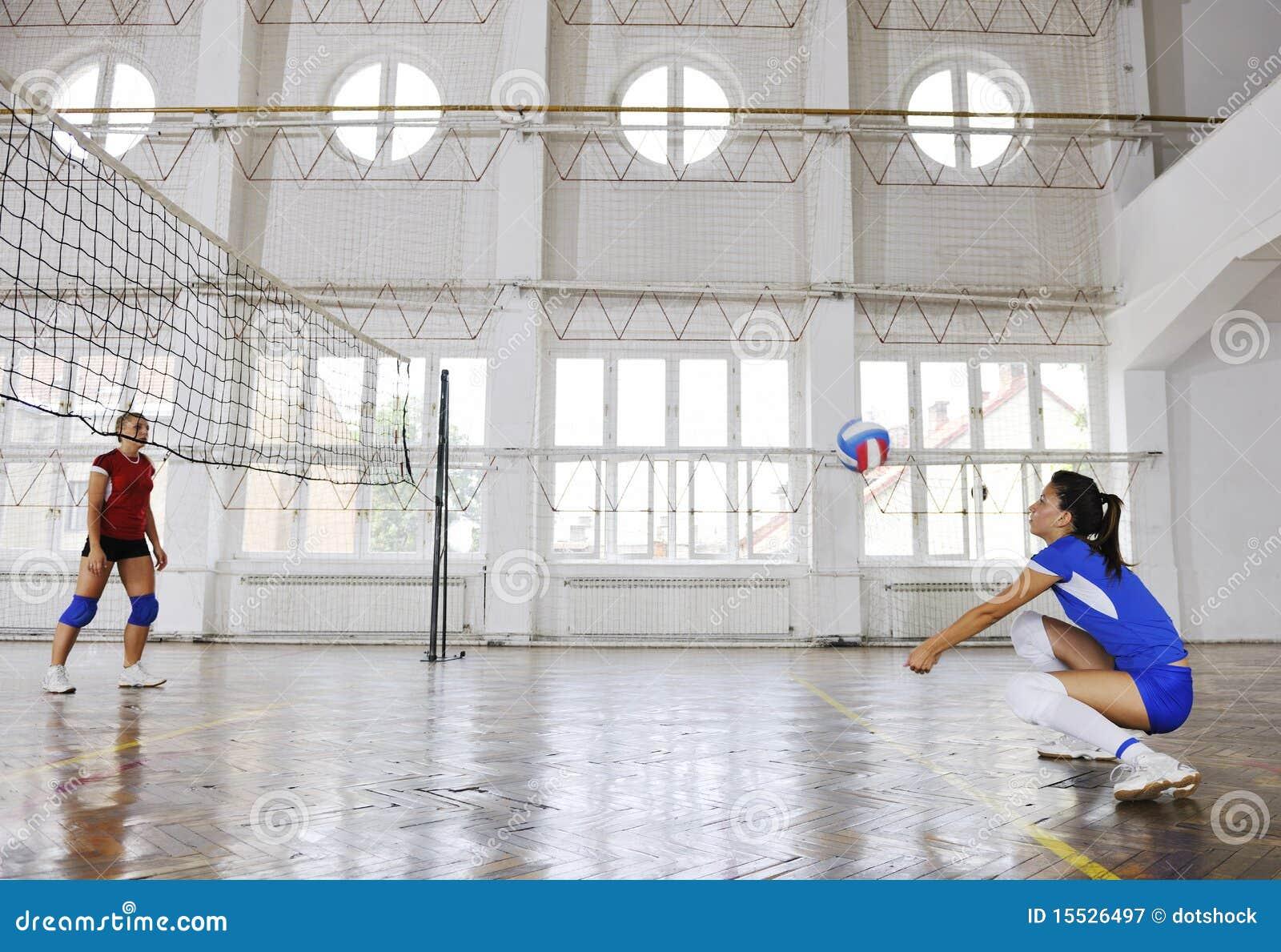 Meninas que jogam o jogo interno do voleibol