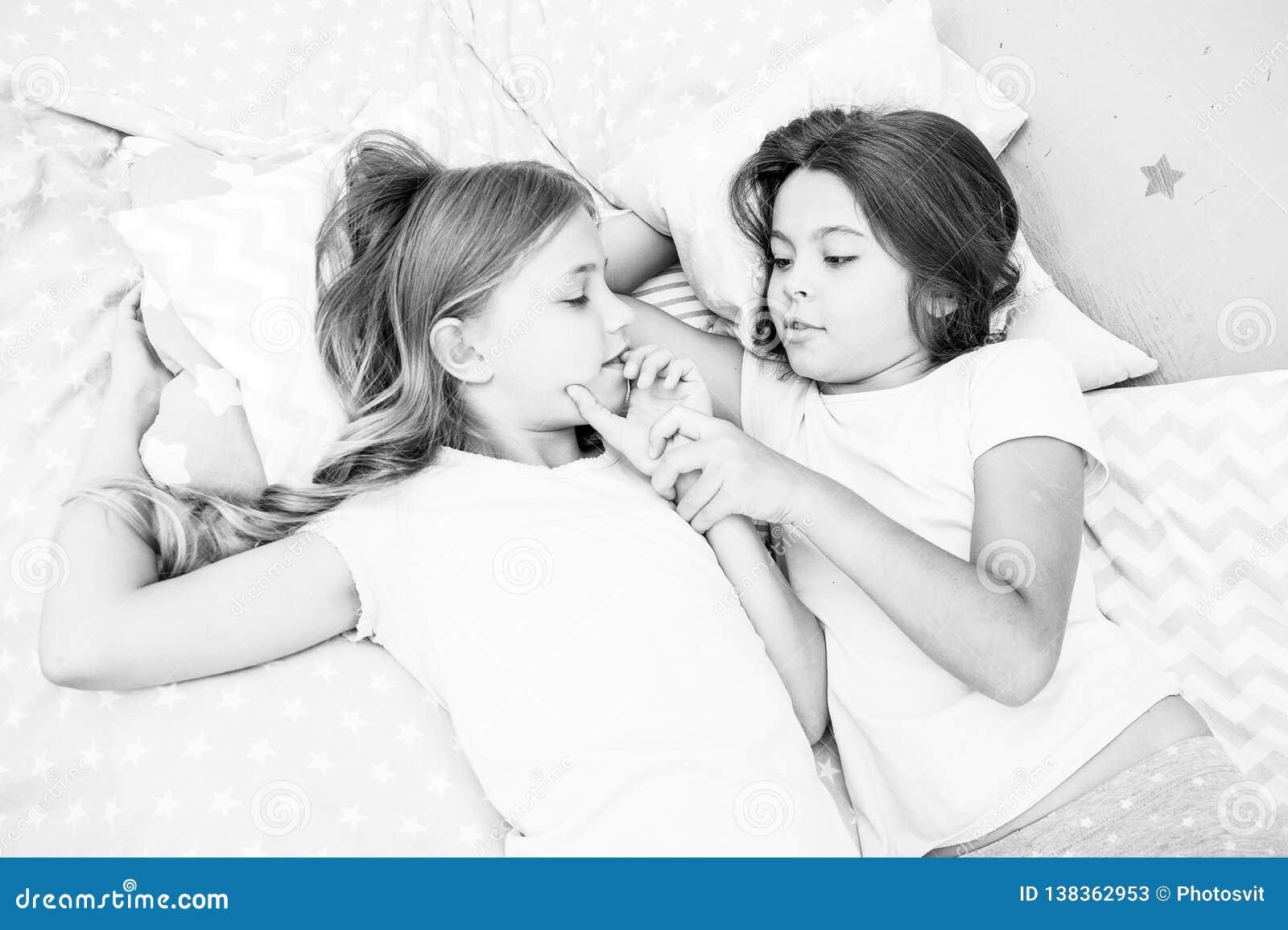 Meninas que relaxam na cama Conceito do partido de descanso As meninas apenas querem ter o divertimento Convide o amigo para o sl