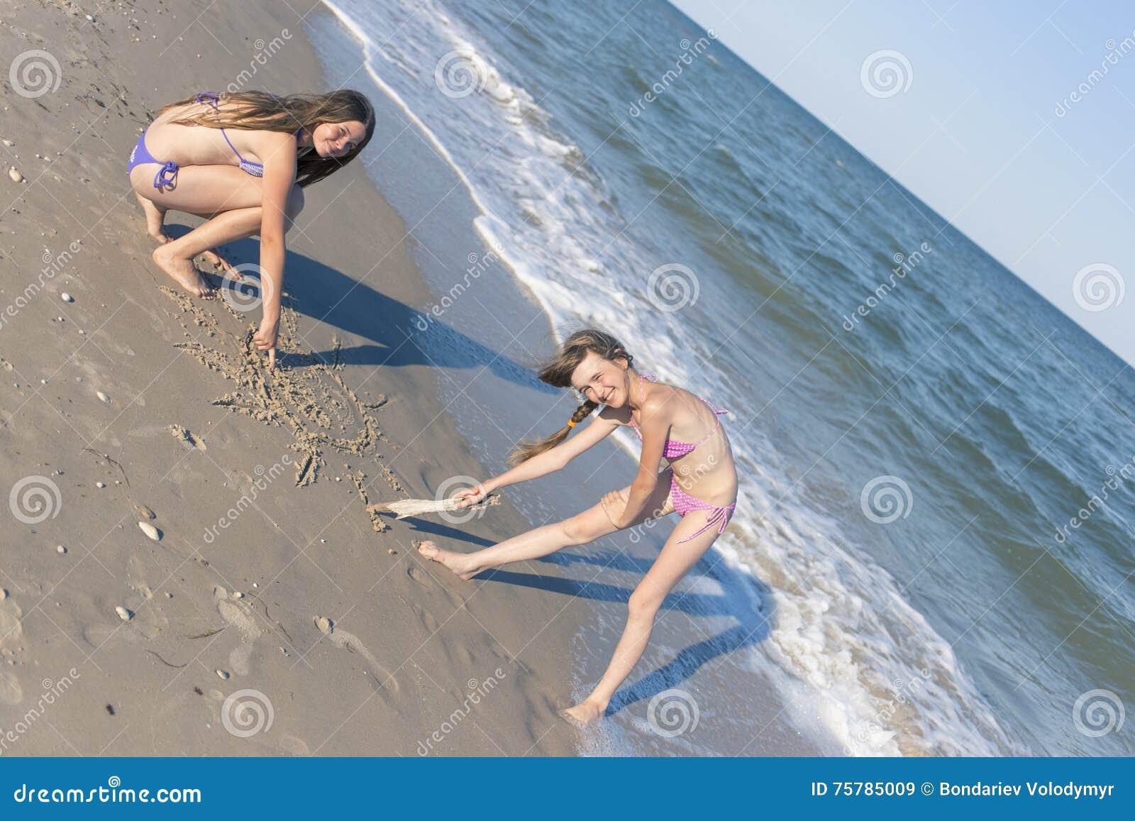 Meninas que tiram na areia na praia no sol do verão