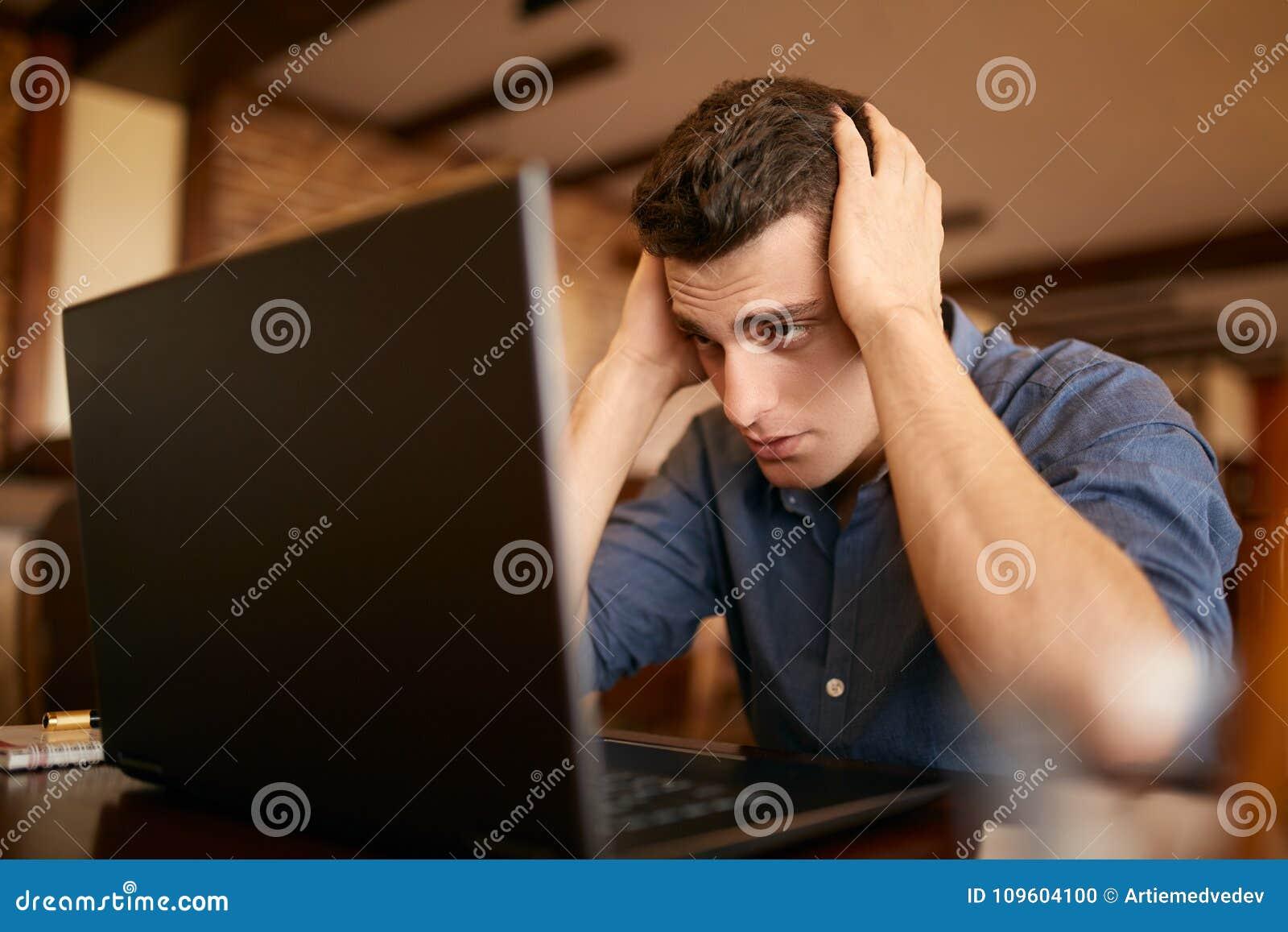 Mening tröttat Frustrerad ung stilig man som ser evakuerad och sjuk, medan sitta på hans arbetsplats med bärbara datorn