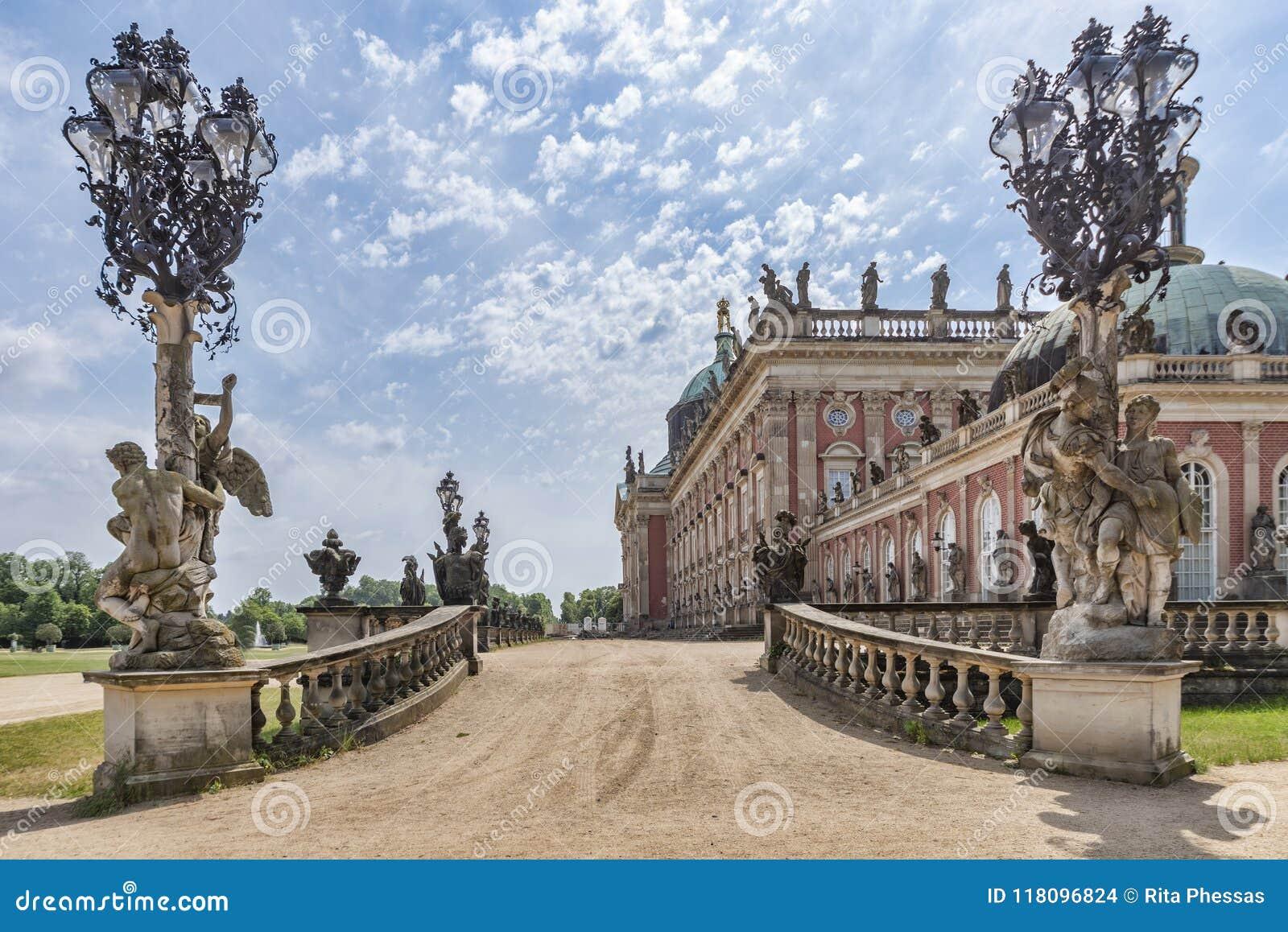 Mening van één van de ingangen van Das Neue Palast met zijn barokke standbeelden, smeedijzerlantaarns, en een deel van de paleist