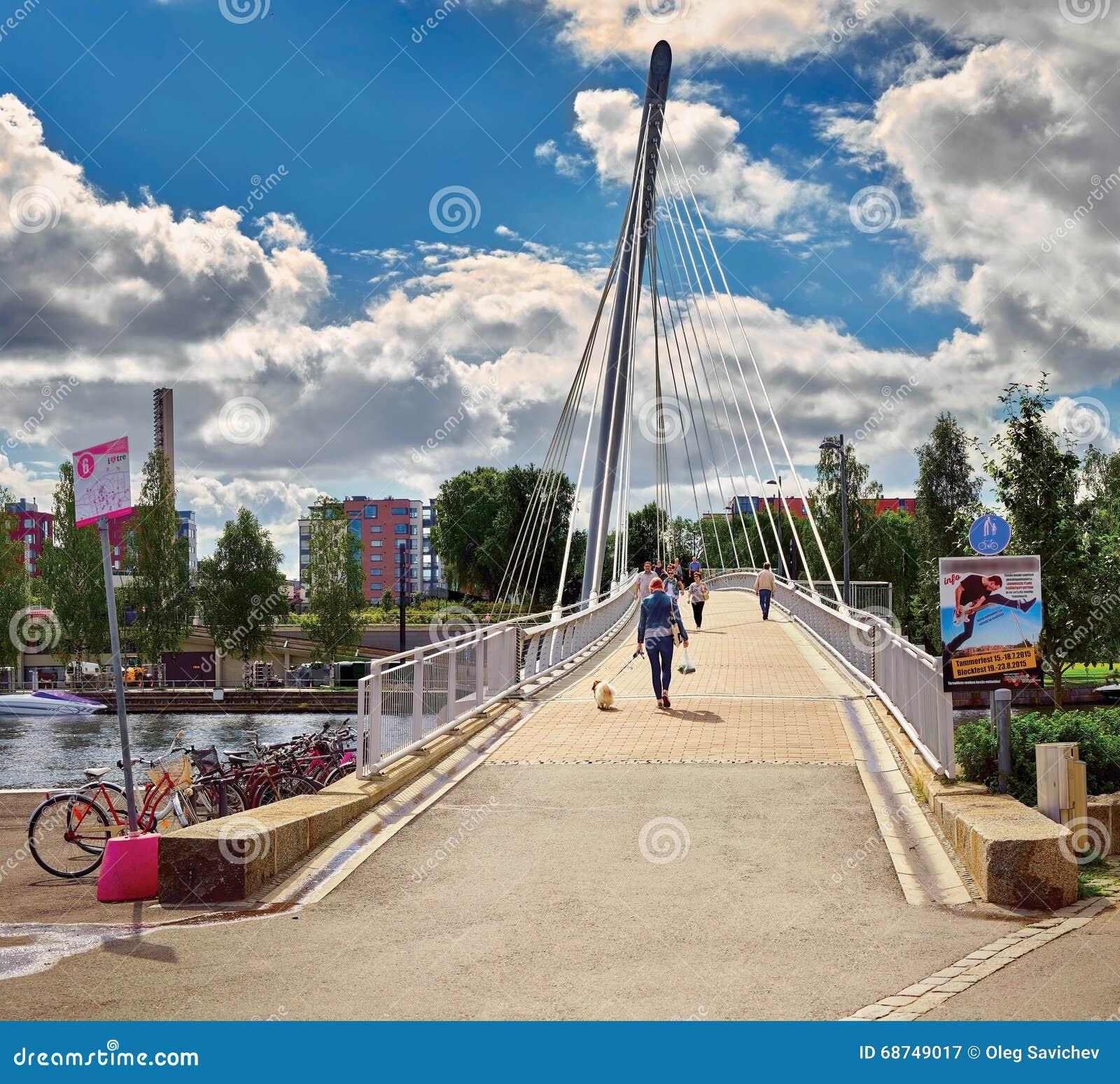 Mening van de brug over de rivier Tammerkoski (Finland, Tampere), met boten op de rivier en de mensen die over br gaan