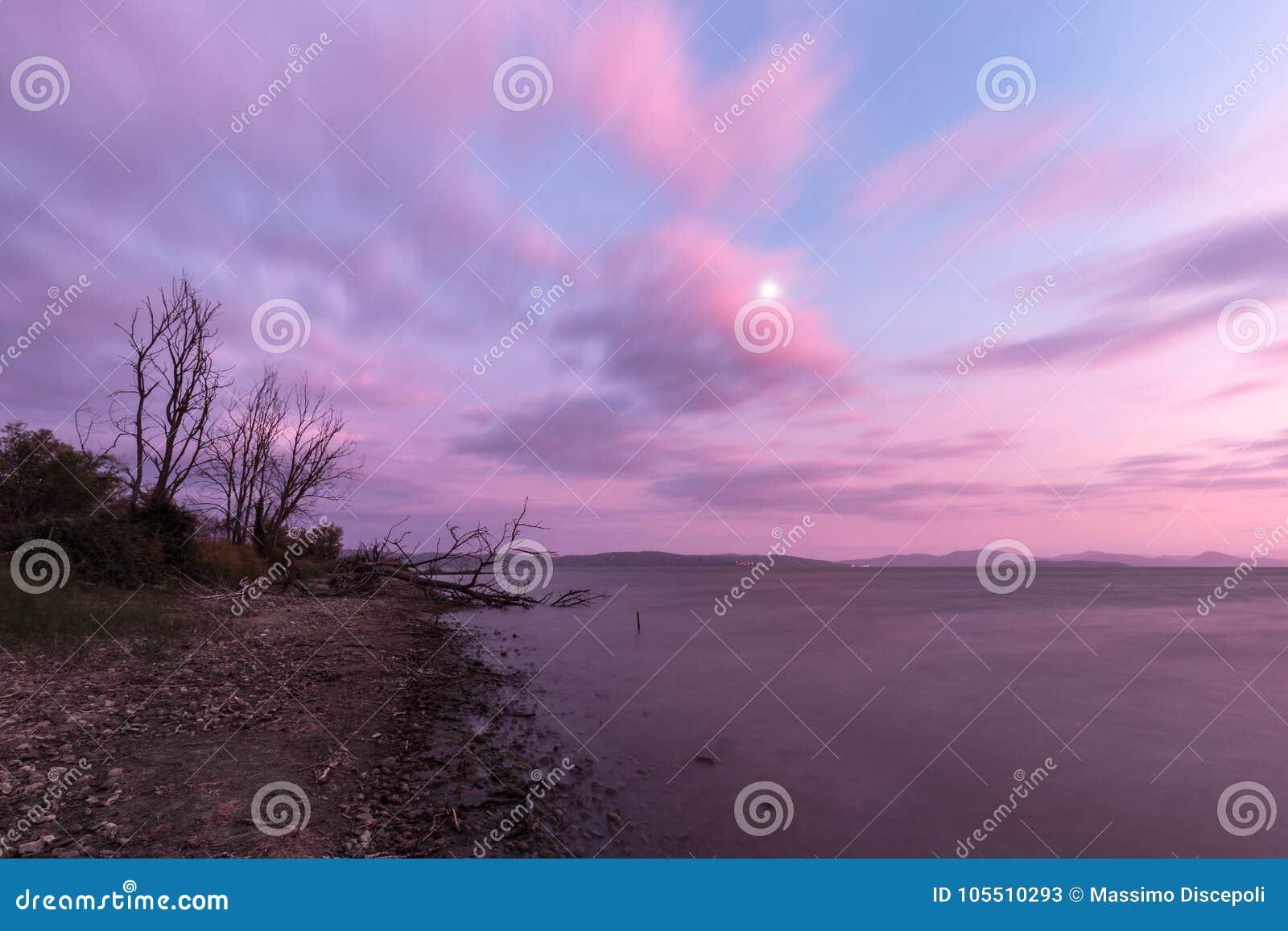 Mening van een meerkust bij zonsondergang, met installaties, bomen, mooie pu