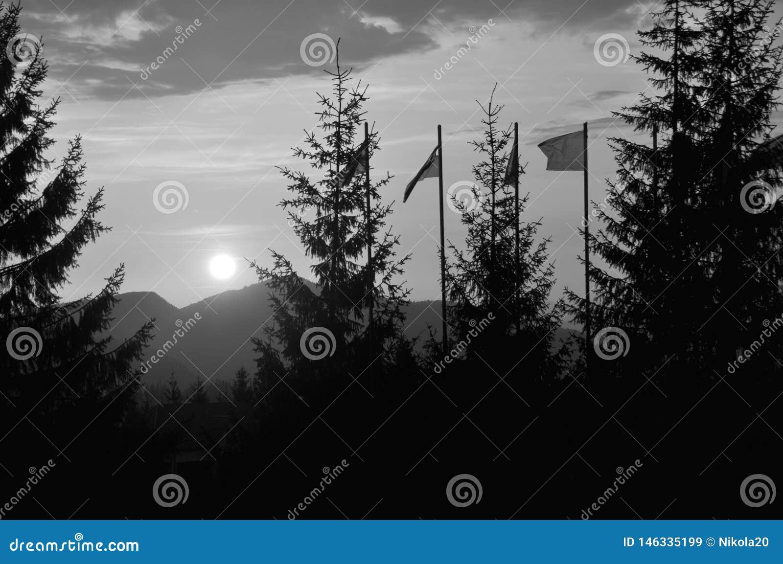 Mening van grote heldere witte zon in dramatische oranje hemel over donkere bergketen bij zonsondergang of zonsopgang in bergen S