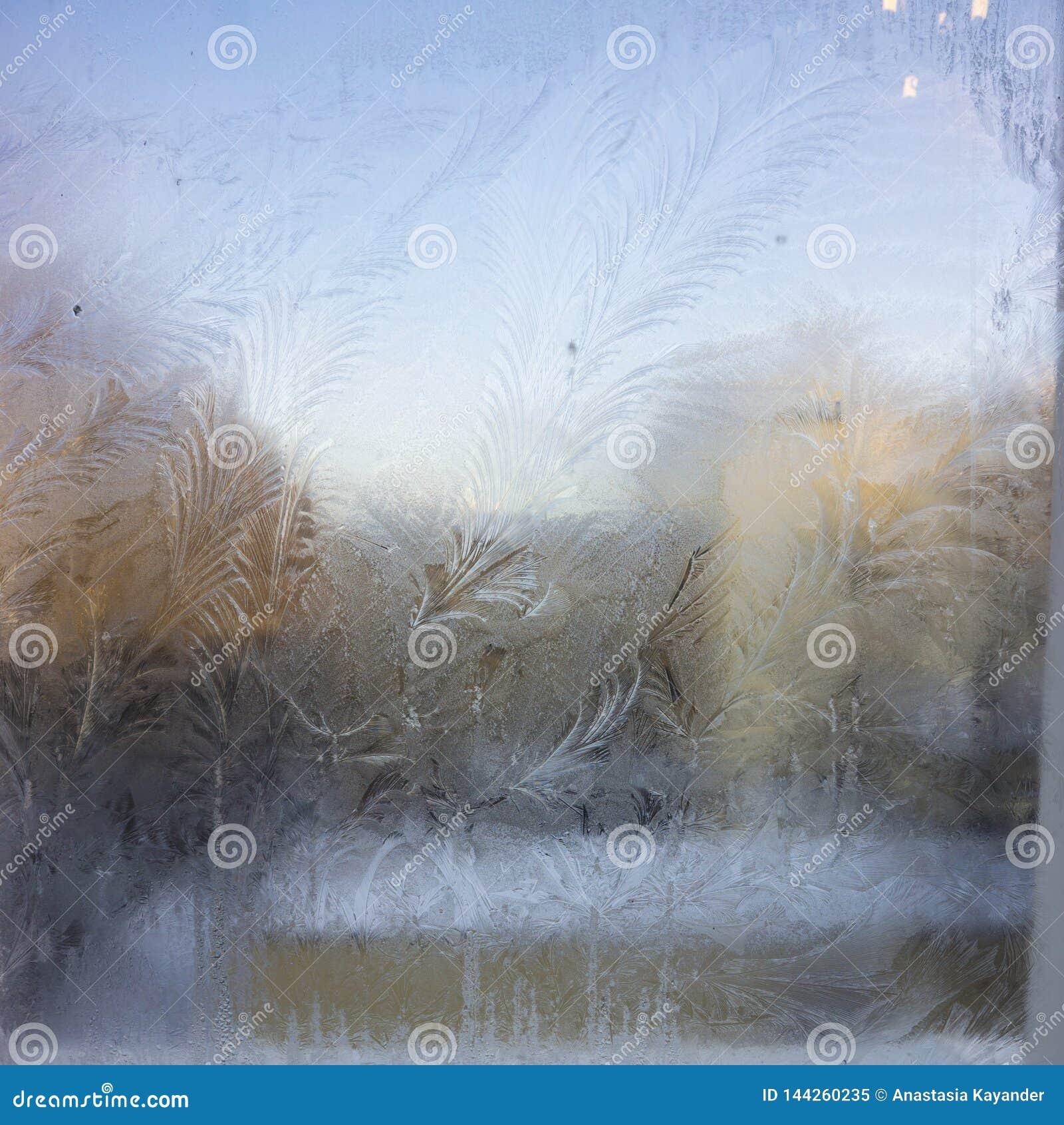 Mening van het oude stadshuis van een bevroren de wintervenster De patronen van het textuurijs op glas Selectieve nadruk