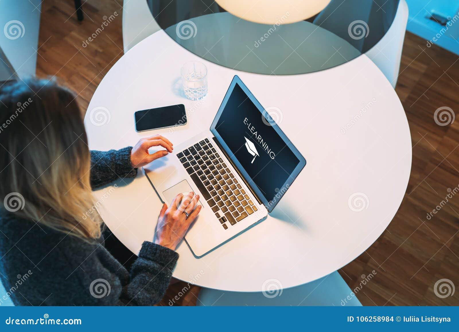 Mening van hierboven Het studentenmeisje zit bij ronde witte lijst en gebruikt laptop met een inschrijving e-Lerend op het scherm