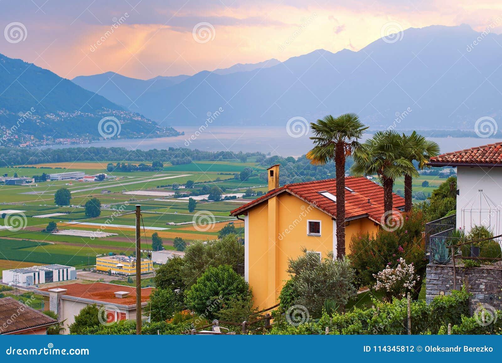 Mening van landelijk Zuidelijk Zwitserland met huizen, landbouwbedrijven, wijngaarden, de bergen en Meer Maggiore van alpen