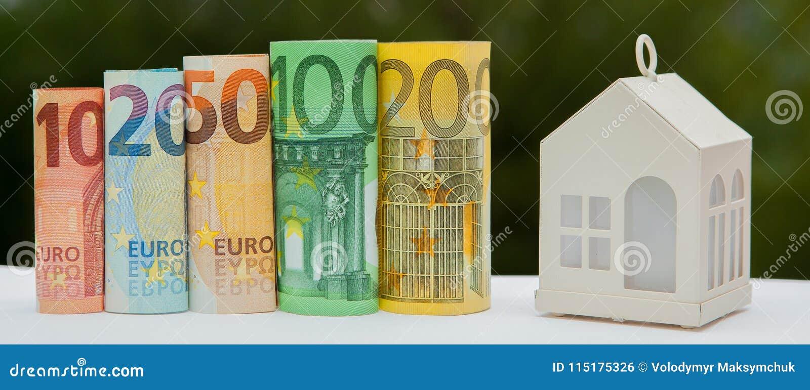 Mening van muntstukstapel met huismodel op groene achtergrond, besparingenplannen voor huisvesting, financieel concept, Hypotheek