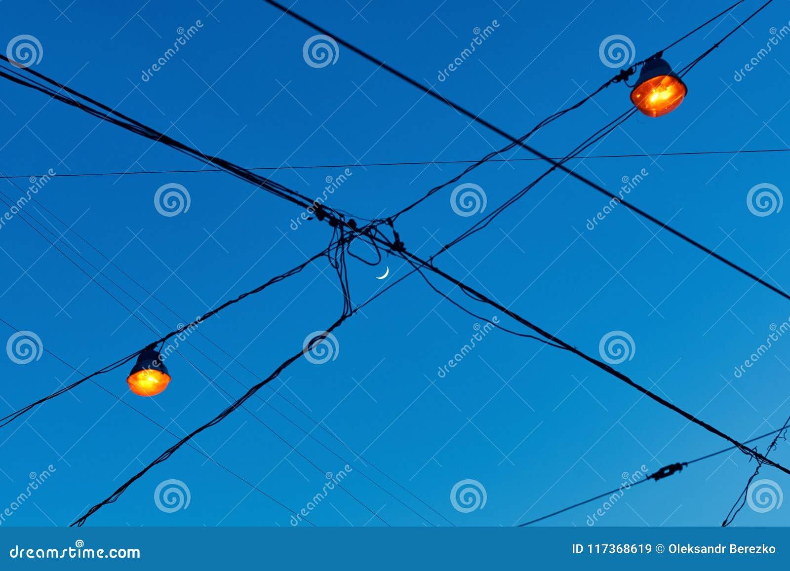 Mening van nieuwe maanhalve maan door de elektrische draden op de straat met lichten die net zijn aangestoken