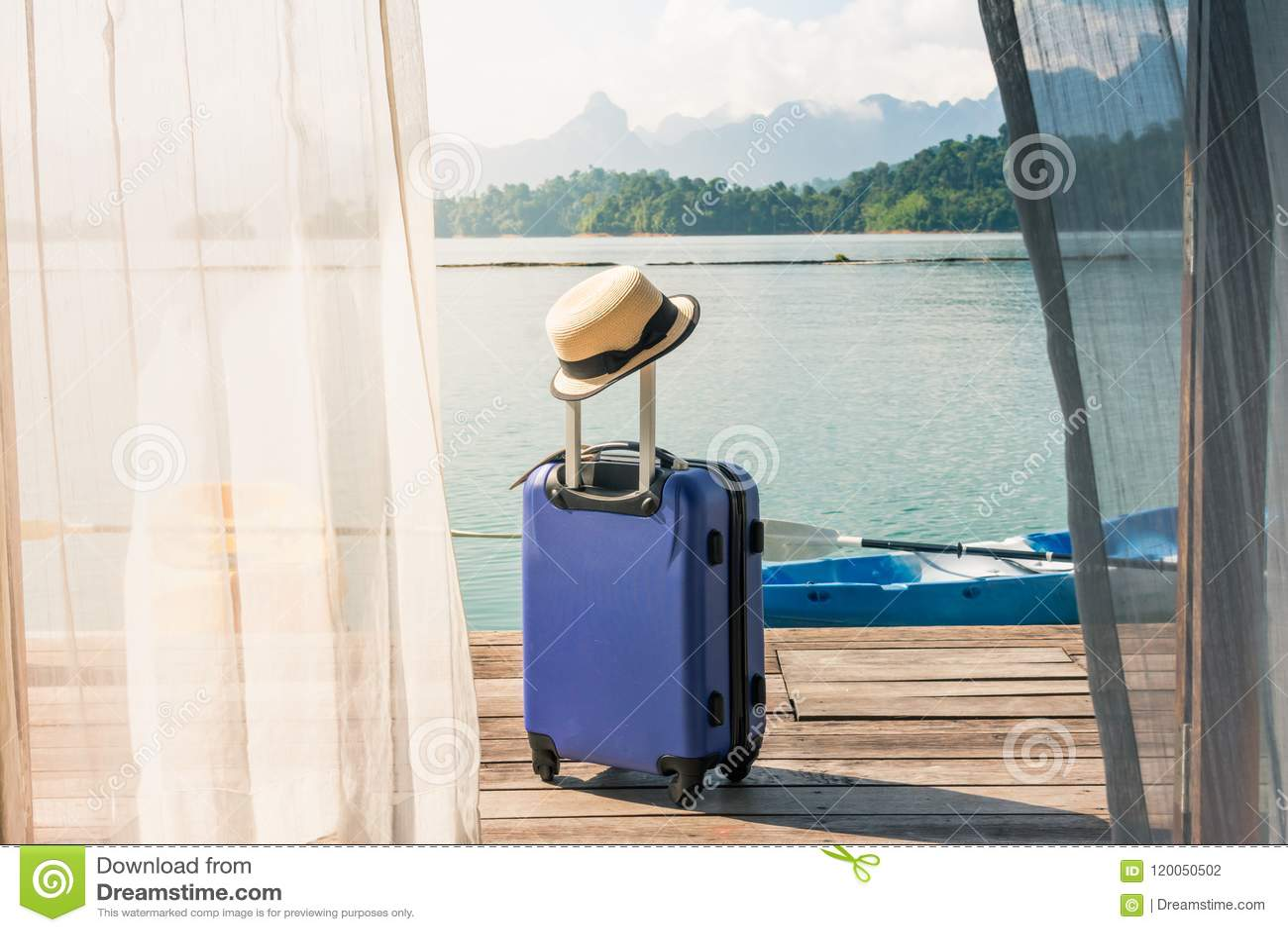 Mening van slaapkamer met venstergordijn en reiskoffer met hoed