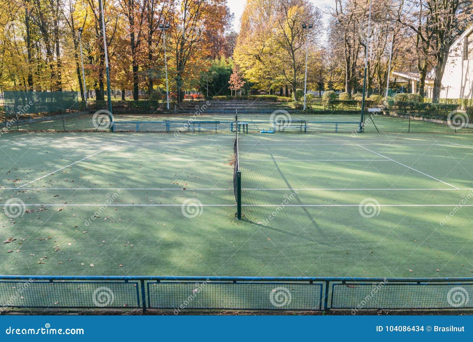Mening van tribunes van twee openlucht lege tennisbanen