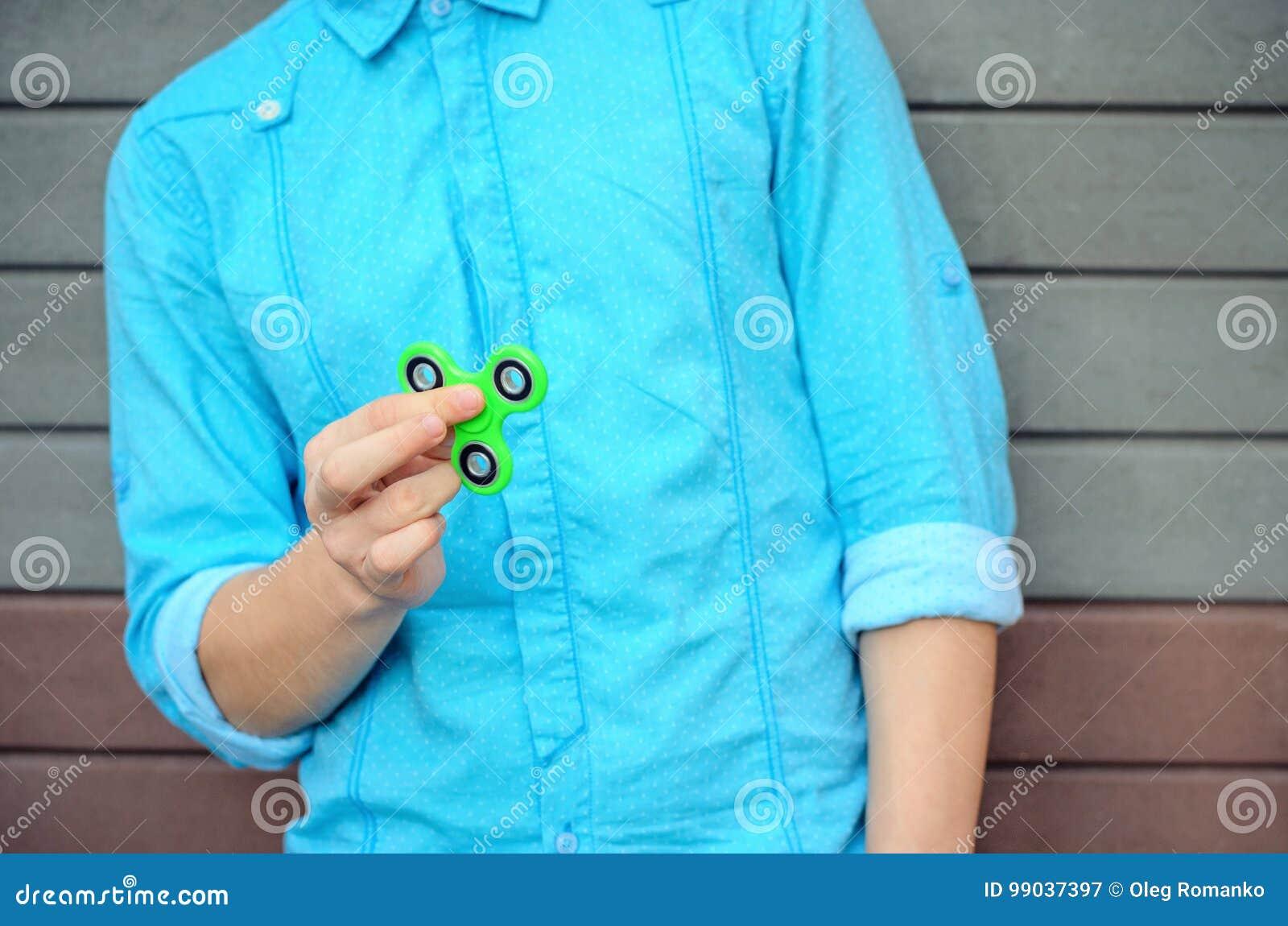 Menino à moda de Yong na mão que guarda a rotação popular da inquietação do dispositivo