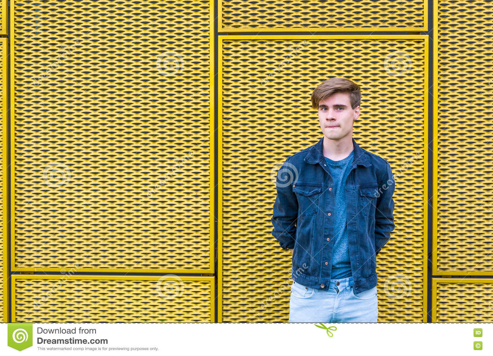 Menino adolescente à moda sobre o pensamento amarelo industrial do fundo
