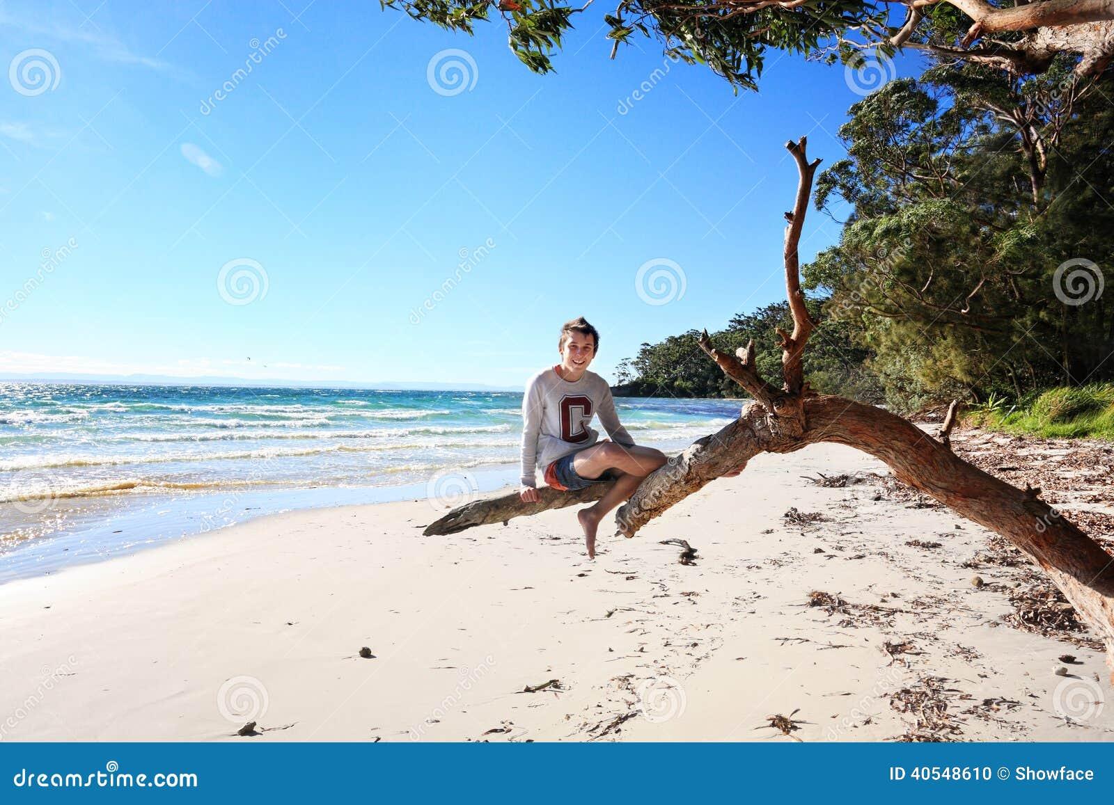 Menino adolescente alegre que senta-se no feriado da árvore na praia Australi