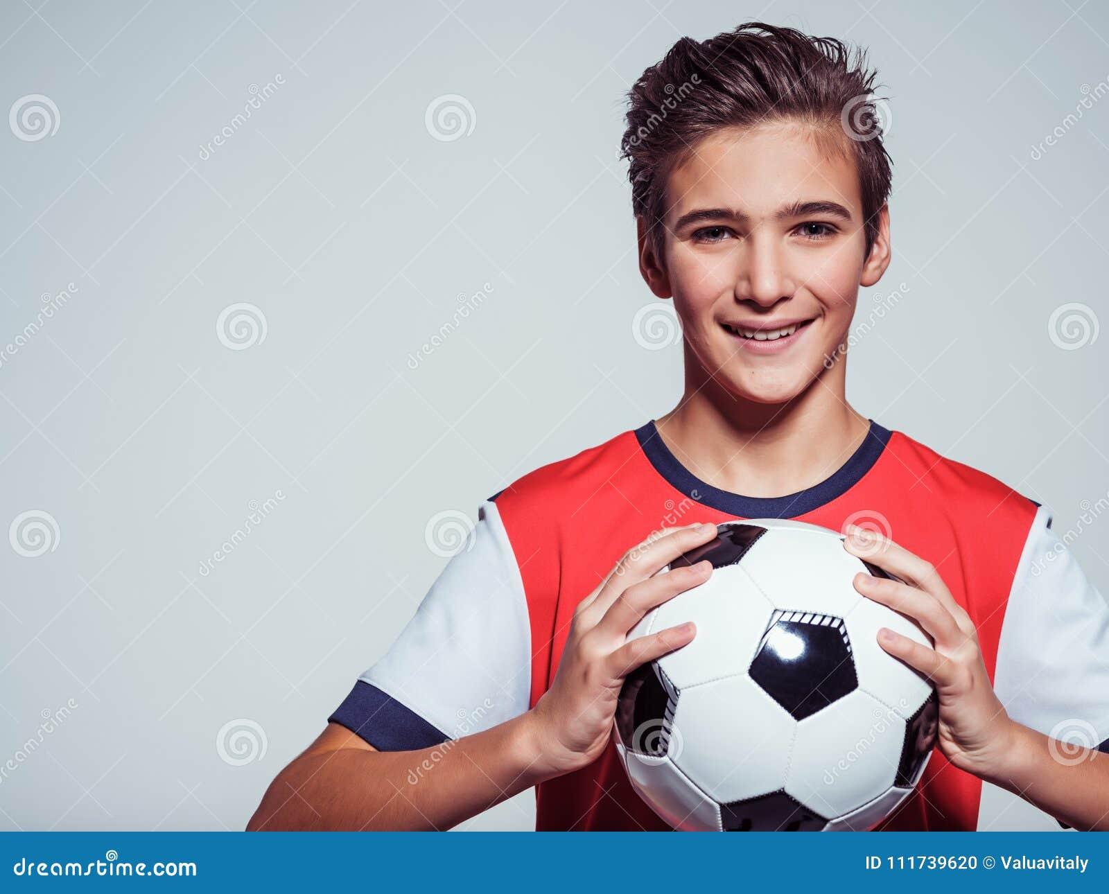 Menino adolescente de sorriso no sportswear que guarda a bola de futebol