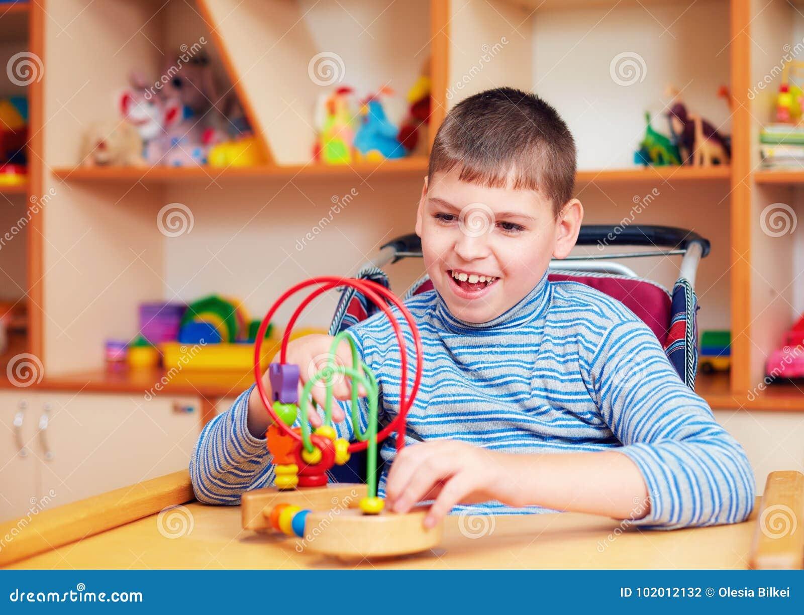 Menino alegre com inabilidade no centro de reabilitação para crianças com necessidades especiais, resolvendo o enigma lógico