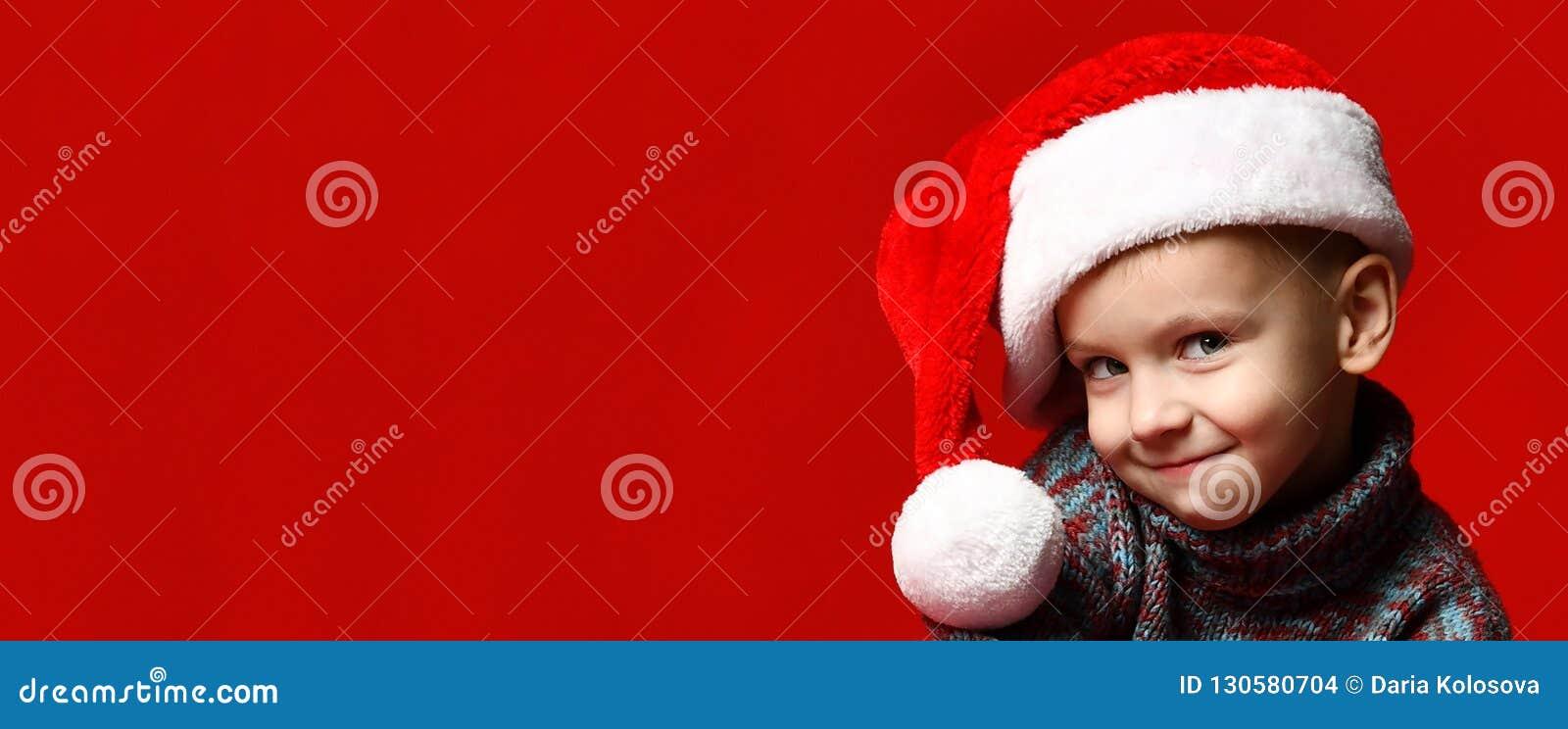 Menino alegre de sorriso engraçado da criança no chapéu vermelho de Santa
