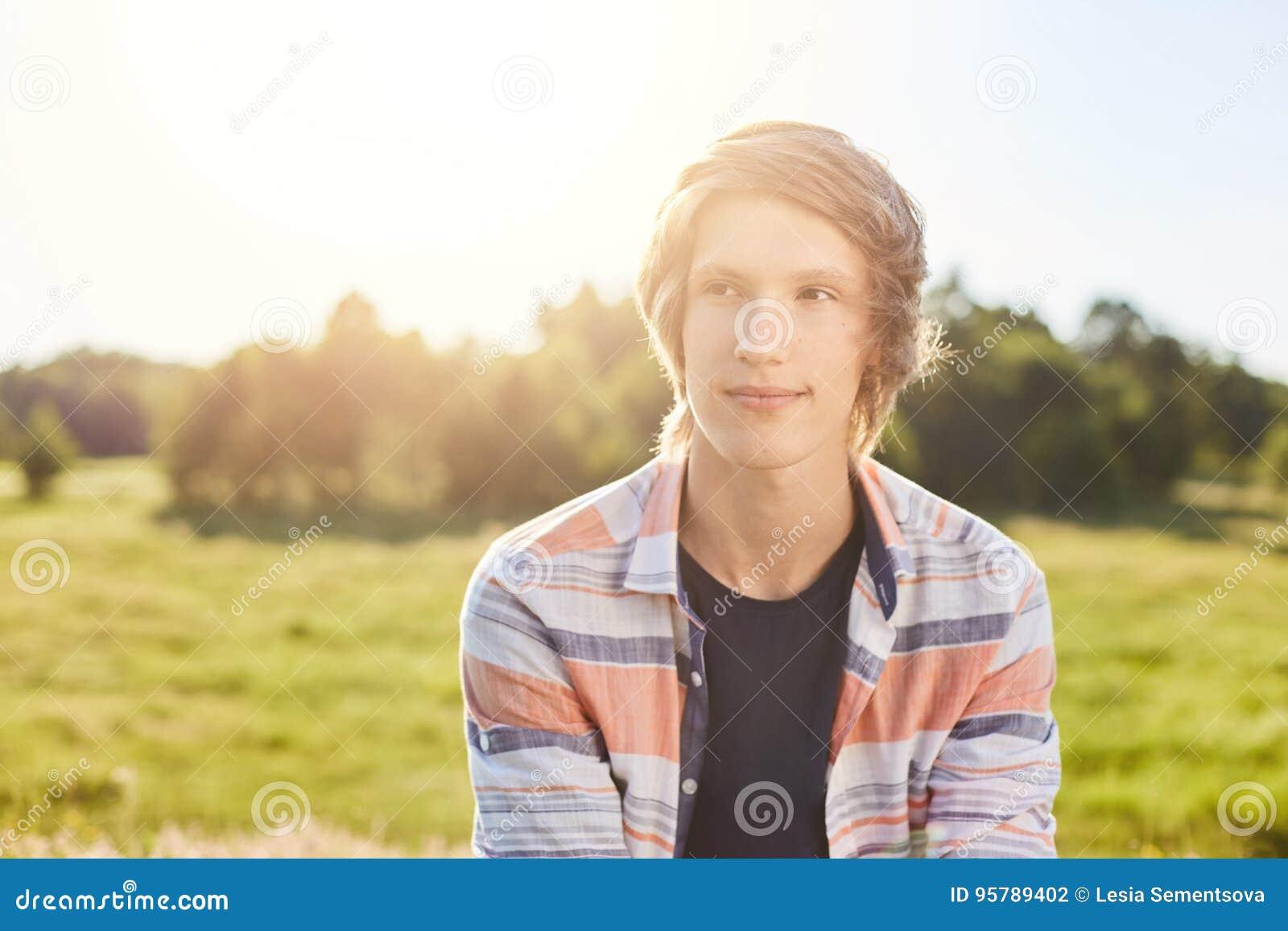 Menino atrativo sonhador com o cabelo leve, os olhos escuros e os bordos finos vestindo a camisa que senta-se sobre o fundo verde