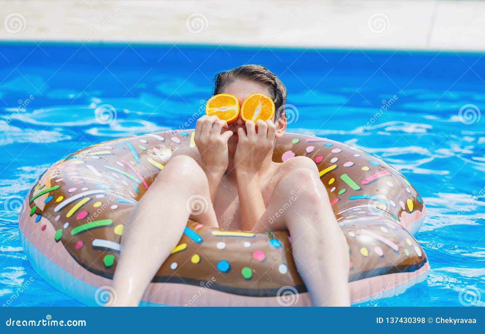 Menino bonito da criança no anel inflável engraçado do flutuador da filhós na piscina com laranjas Adolescente que aprende nadar