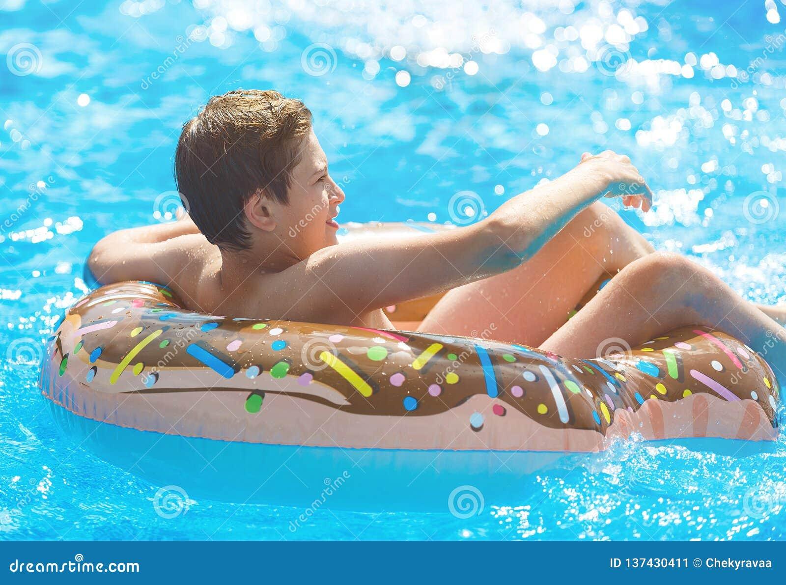 Menino bonito da criança no anel inflável engraçado do flutuador da filhós na piscina com laranjas O adolescente que aprende nada