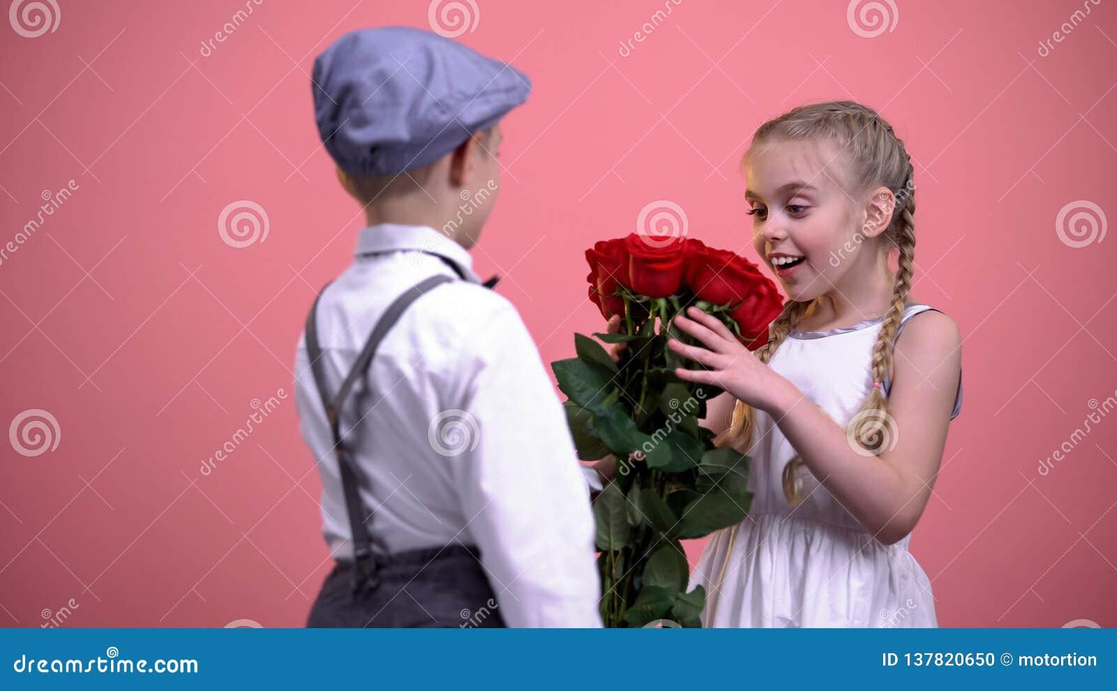 Menino bonito na roupa do vintage que gifting rosas à menina bonita nova, primeiro amor