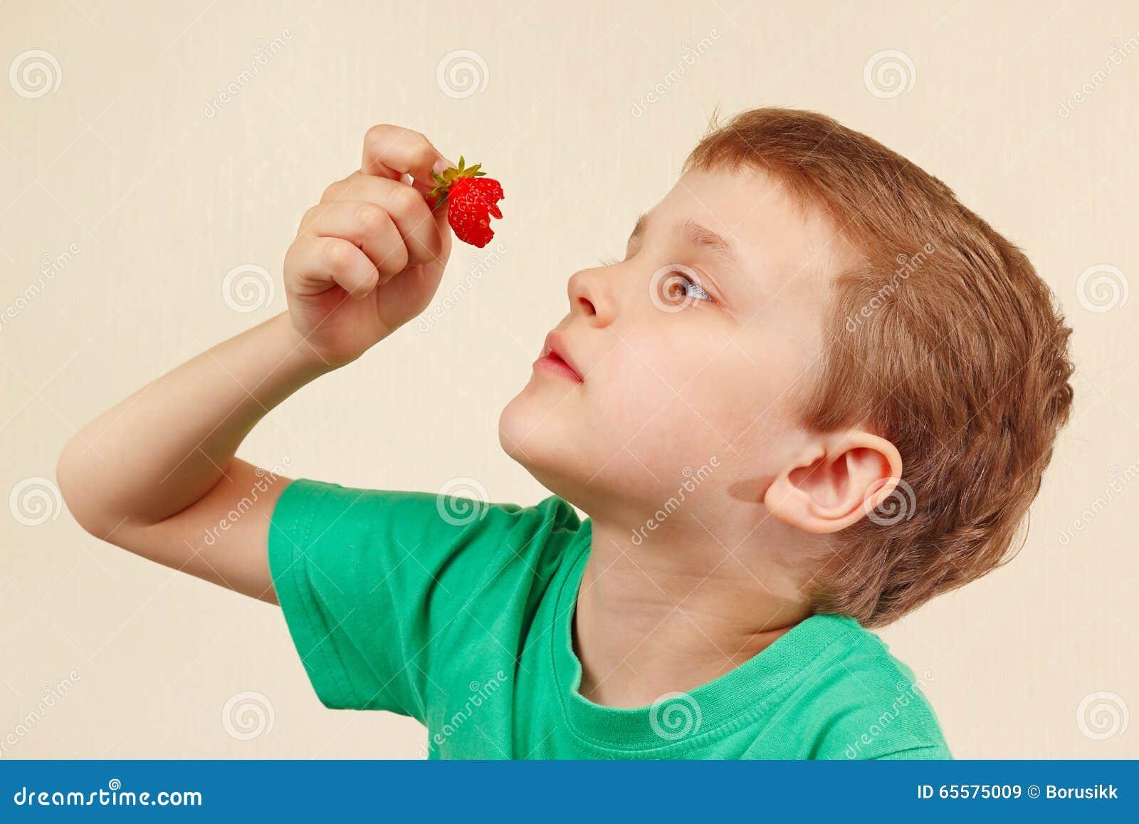 Menino bonito novo que come a morango doce fresca