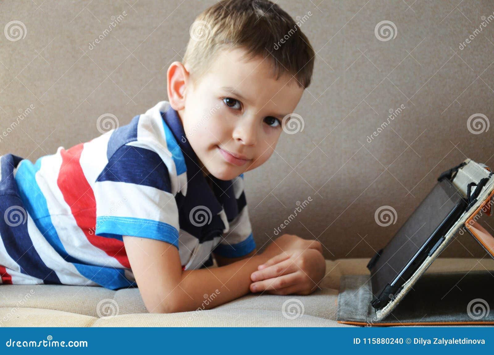 Menino bonito pequeno em um t-shirt verde que joga jogos em uma tabuleta e que olha desenhos animados Criança com tabuleta