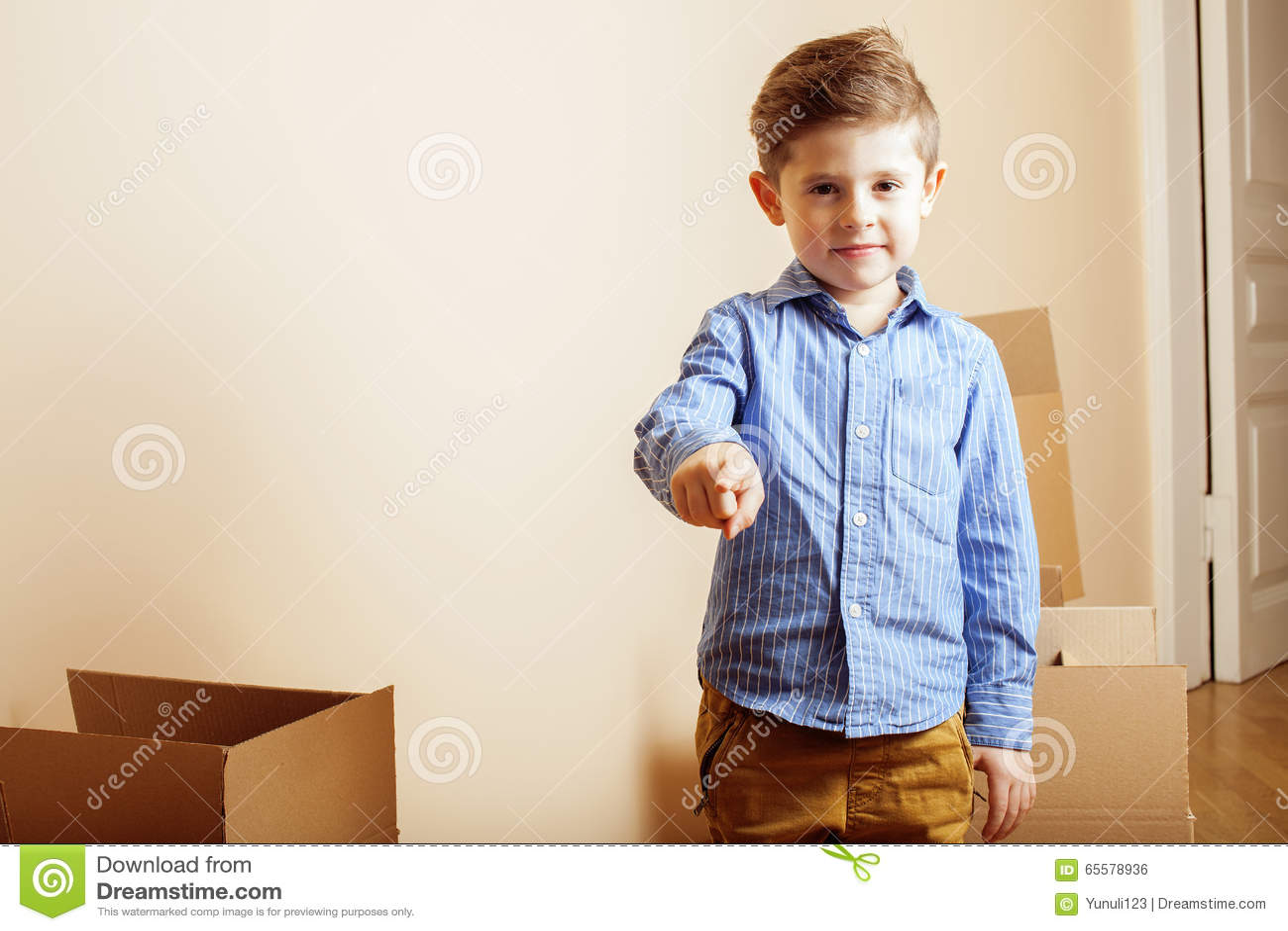 Menino bonito pequeno na sala vazia, remoove à casa nova as caixas sozinhas home do emong fecham-se acima da criança