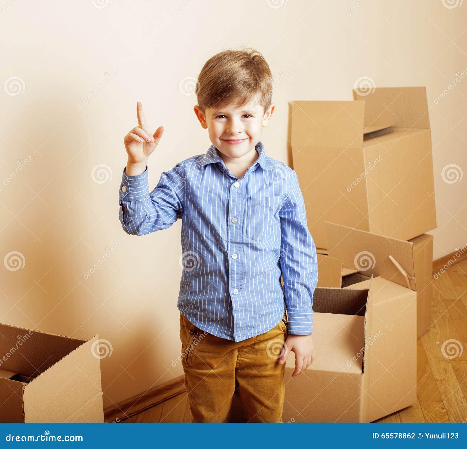 Menino bonito pequeno na sala vazia, remoove à casa nova caixas sozinhas home do emong