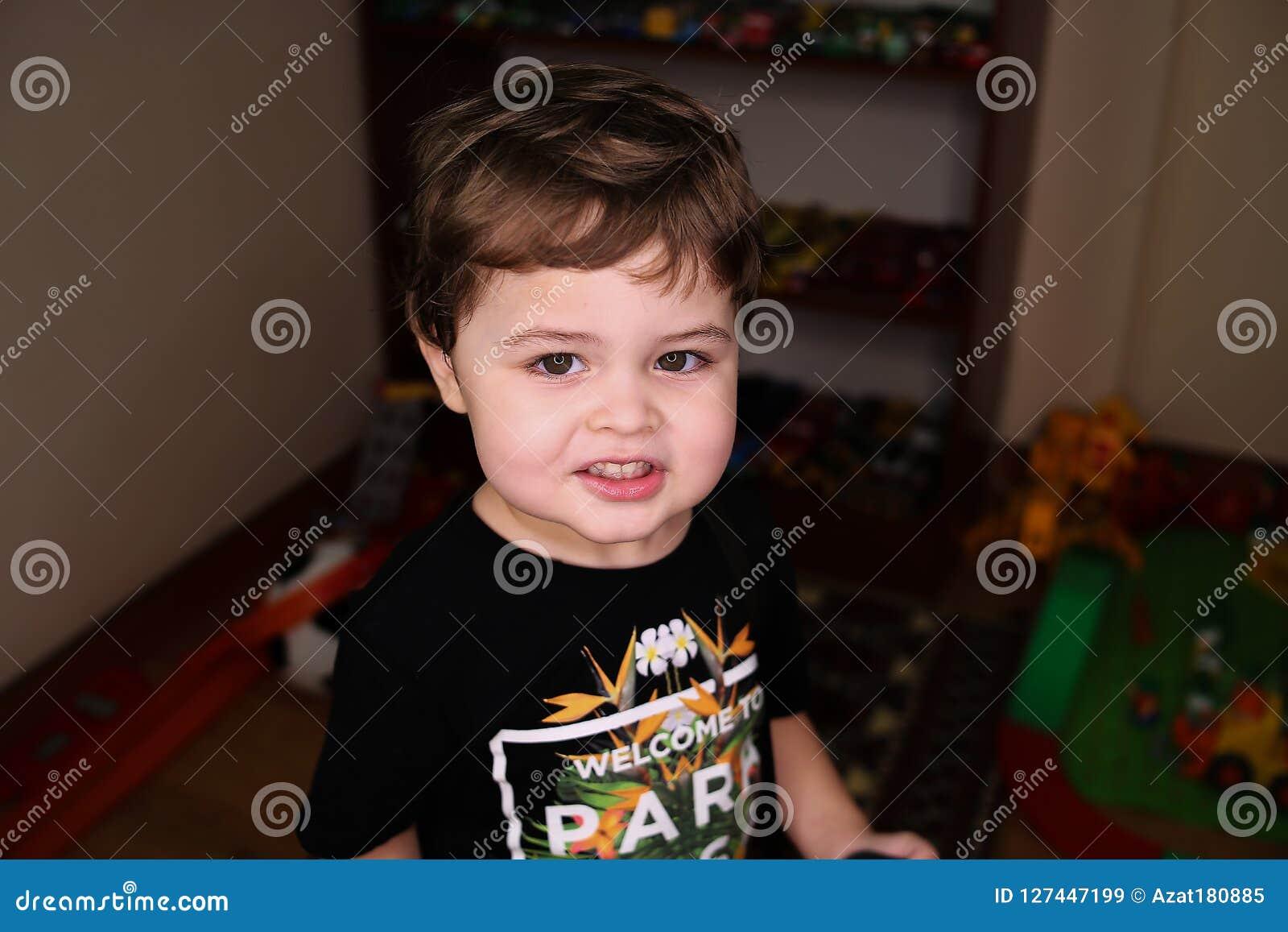 Menino bonito pequeno no sorriso preto do t-shirt