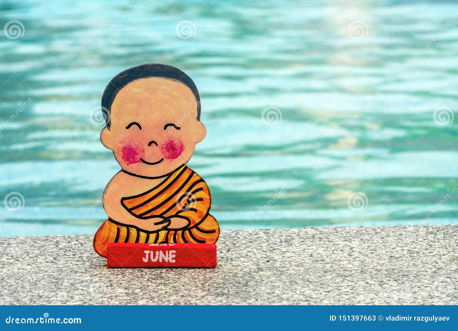 Menino budista nas férias que sentam-se no verão feliz da posição de Lotus na borda da associação Feche acima, copie o espa?o Sin