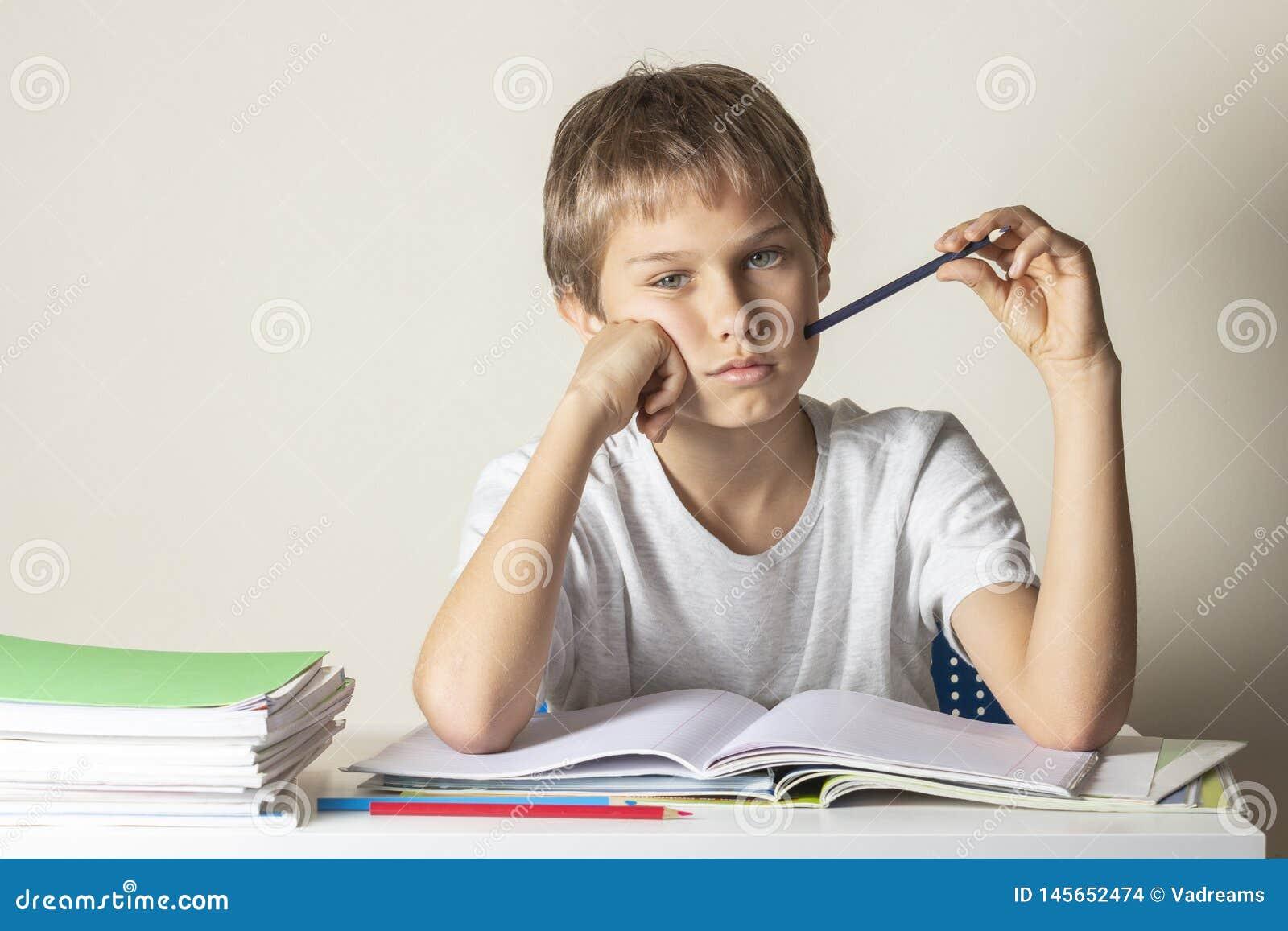 Menino cansado triste que faz trabalhos de casa Educa??o, escola, conceito das dificuldades de aprendizagem