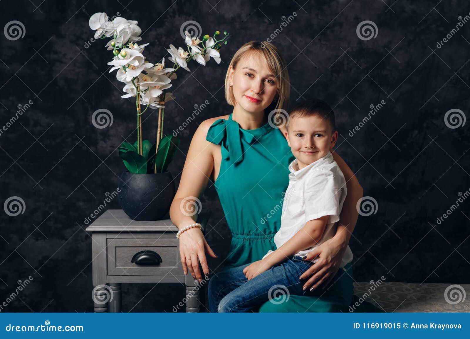 Menino caucasiano do prescholler do pai fêmea e do filho que senta-se junto no sofá dentro Feriado feliz do dia da mãe