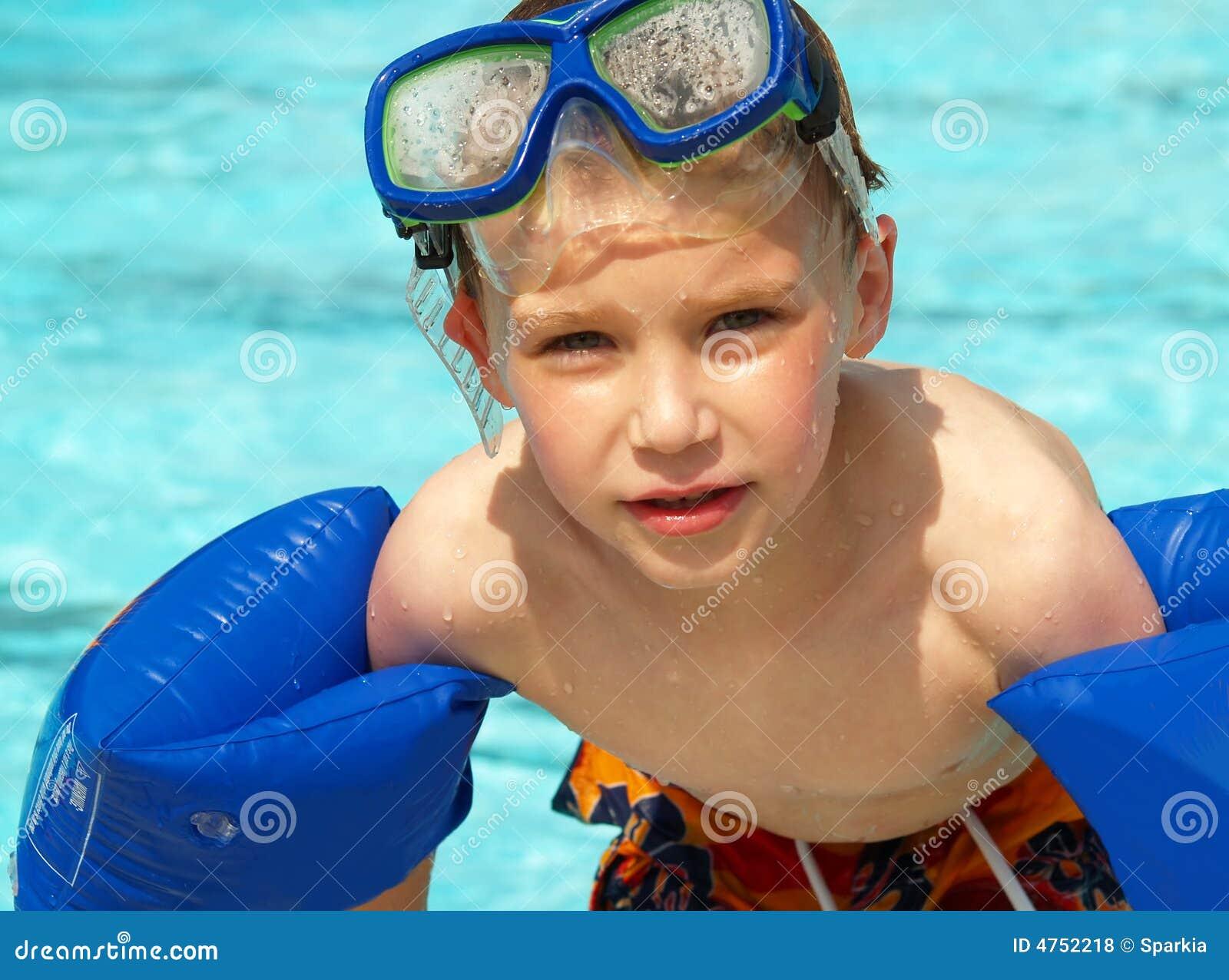 Menino com flutuadores e máscara da nadada