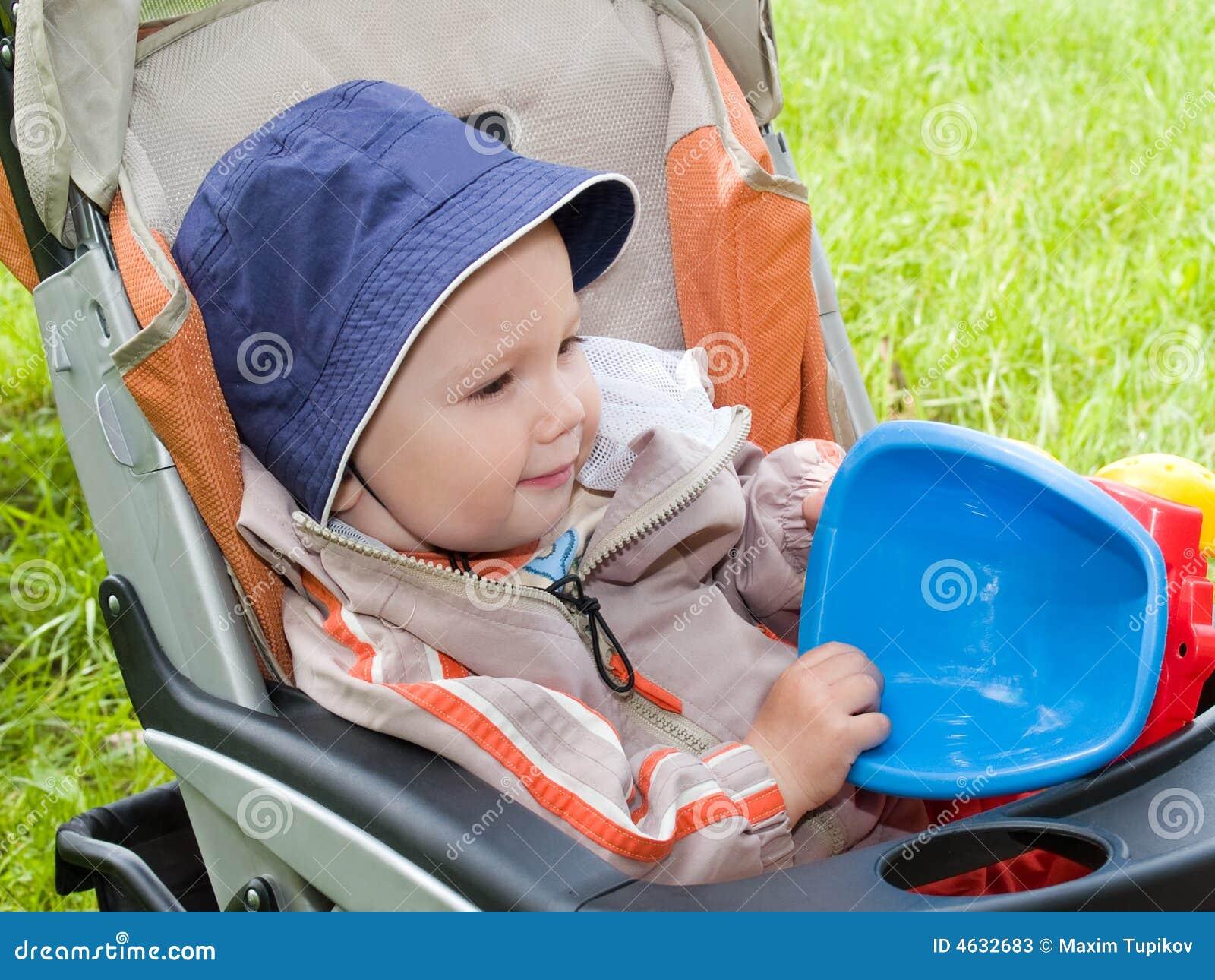 Menino com o brinquedo no carrinho de criança fora